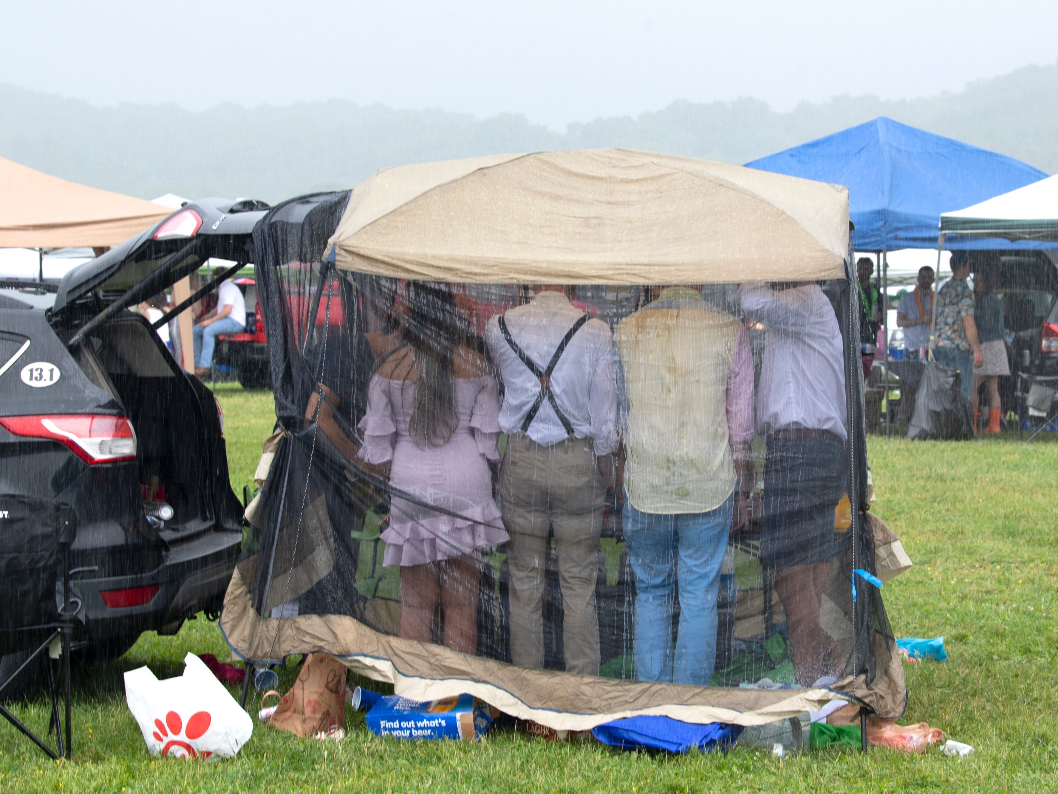 Spectators huddle in a tent from the rain during the 78th Iroquois Steeplechase at Percy Warner Park in Nashville on Saturday, May 11, 2019.