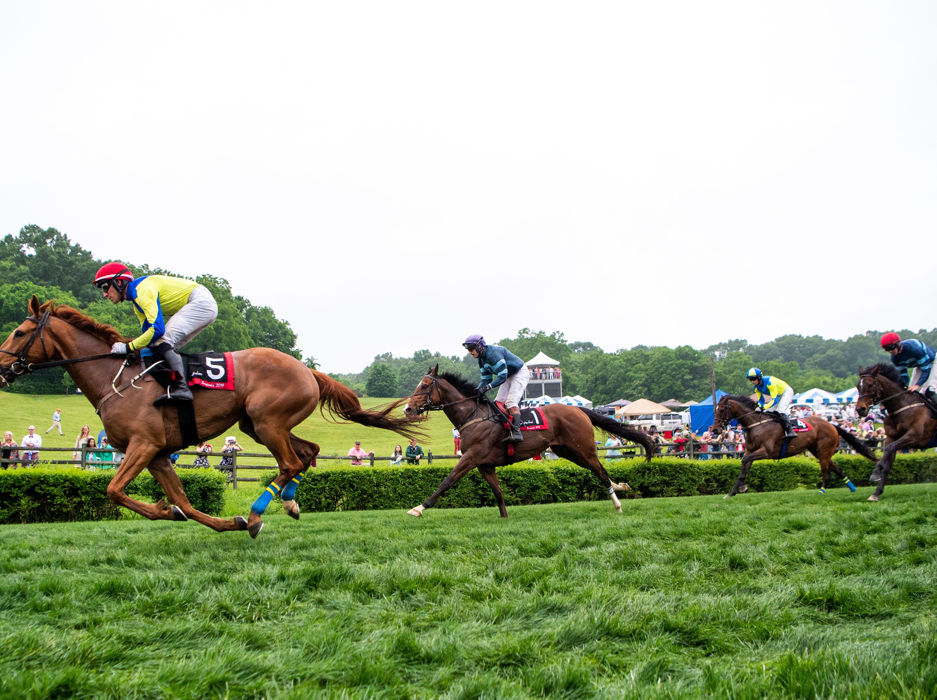 Willie McCarthy and Jaleo, left, speed down the track during the final race of the Iroquois Steeplechase at Percy Warner Park Saturday, May 11, 2019, in Nashville, Tenn.