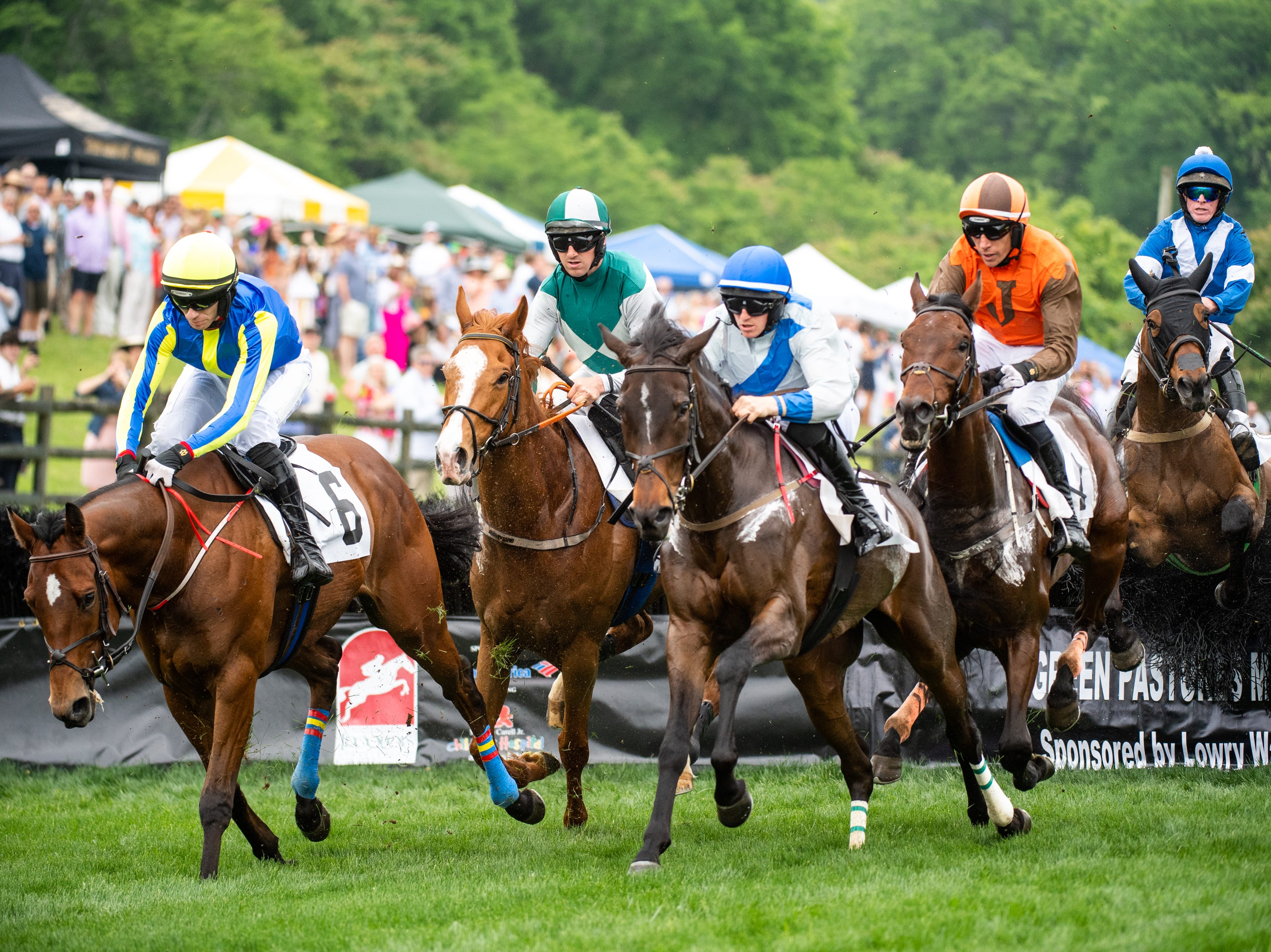 Horses and jockeys complete a jump during the first race of the Iroquois Steeplechase at Percy Warner Park Saturday, May 11, 2019, in Nashville, Tenn.