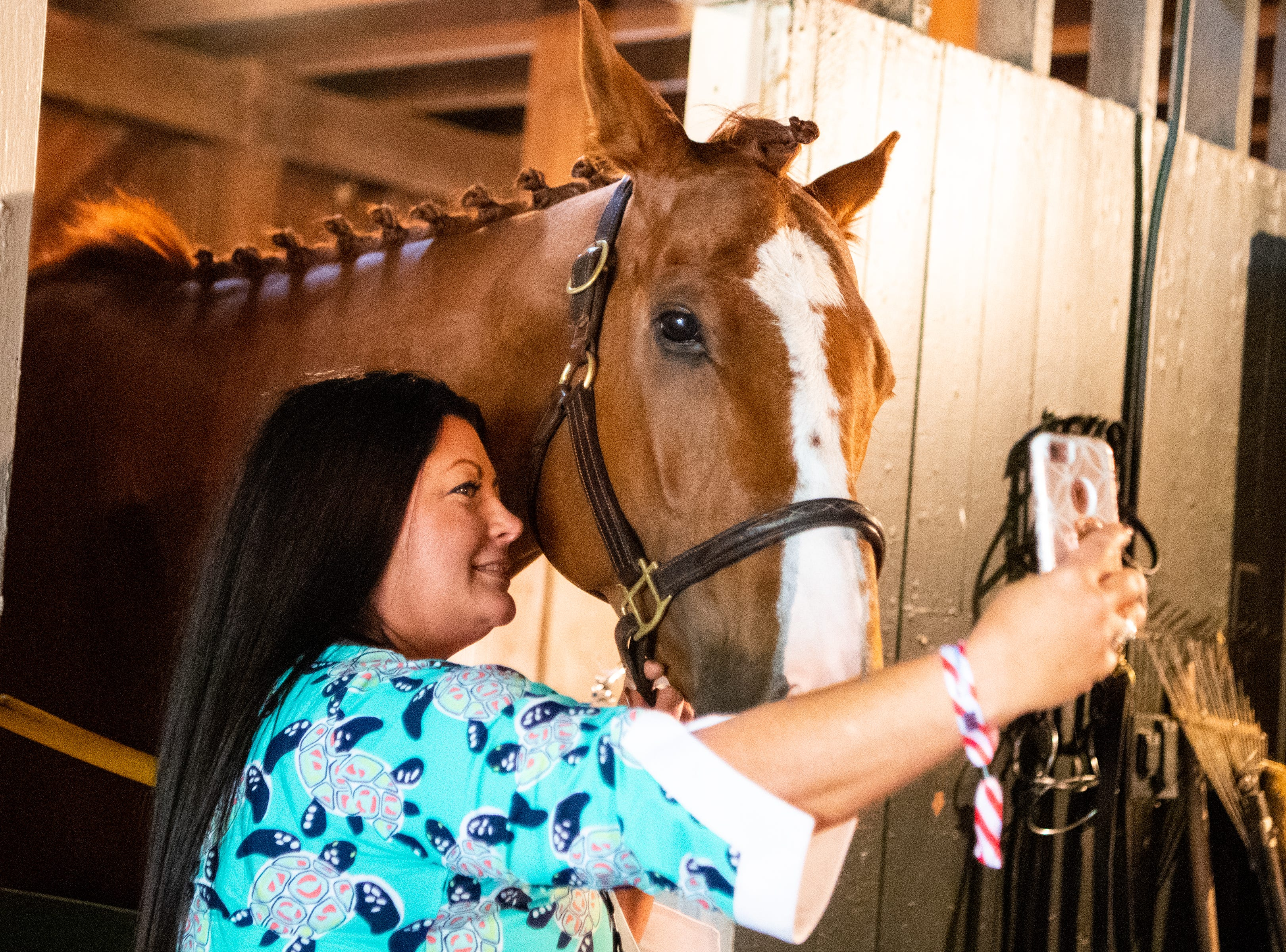 Jennifer Moody takes a selfie with a horse during the Iroquois Steeplechase at Percy Warner Park Saturday, May 11, 2019, in Nashville, Tenn.