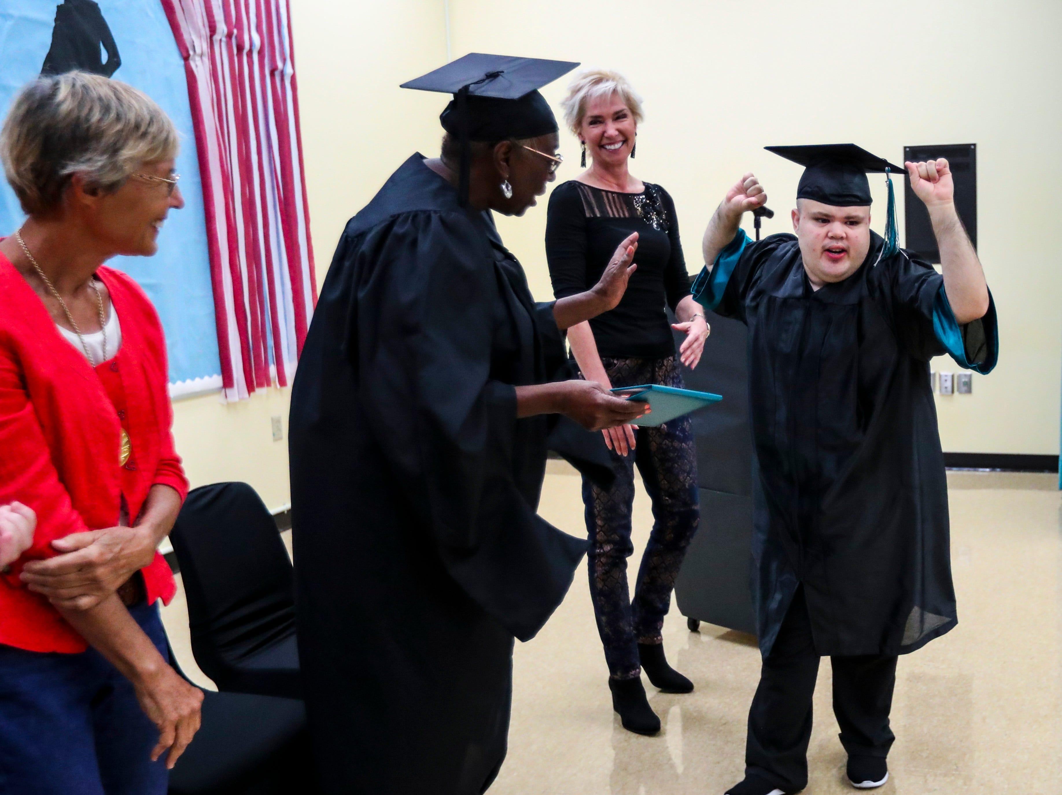 Daviel Deras was excited to receive his diploma. School Board member, Gwynetta Gittens, handed out the diplomas to the students. Ruthie Lohmeyer, Principal, looks on.  13 students at Buckingham Exceptional Student Center graduated during a ceremony in their honor. Family, friends, and staff were there to honor the graduates.