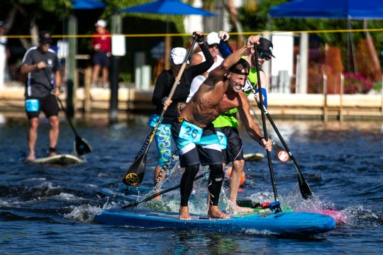 Competitors take off from the starting line in the professional stand up paddleboard race category Saturday, May 11, 2019, during the 43rd annual Great Dock Canoe Race at Crayton Cove in Naples.
