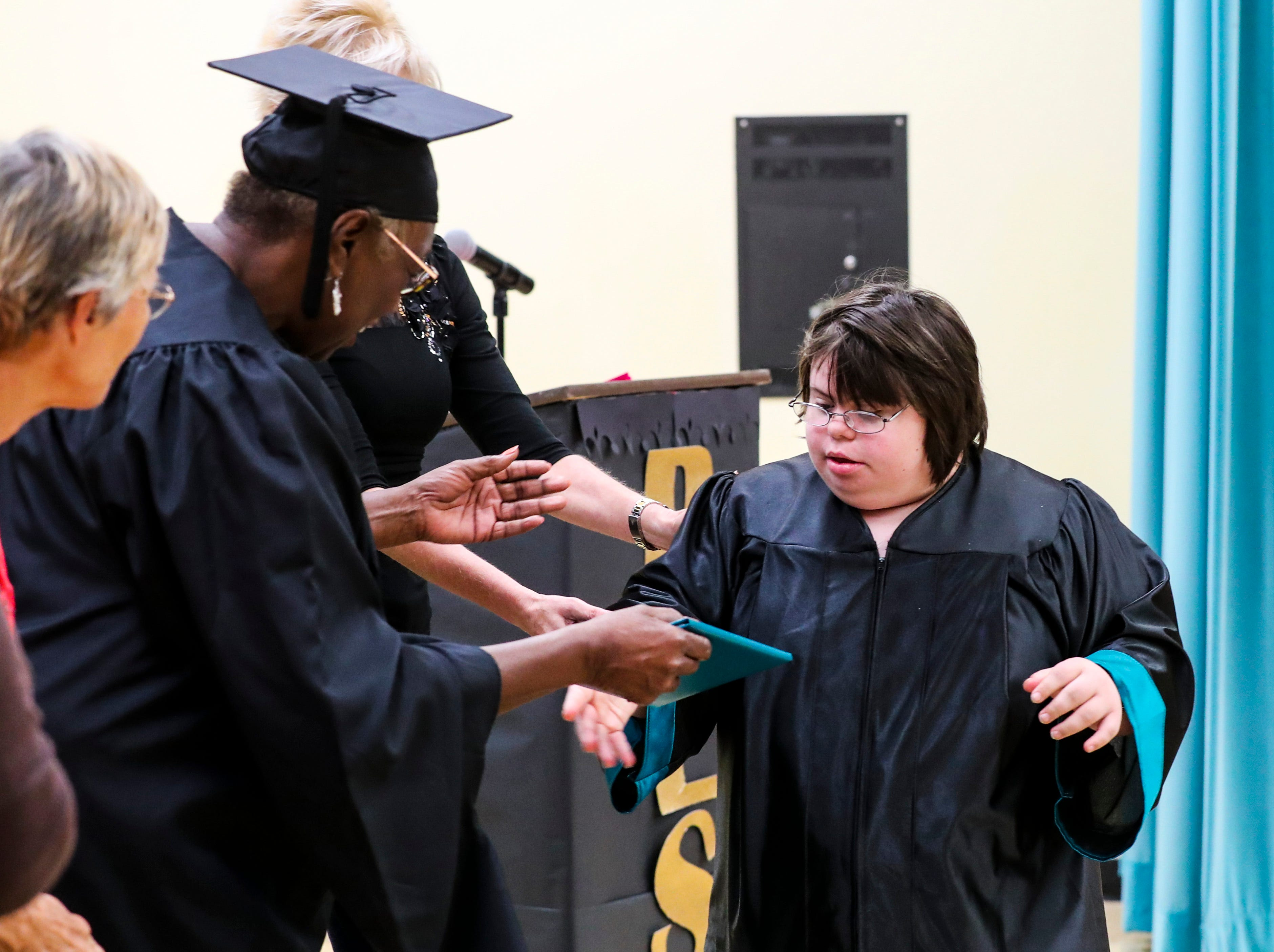 Megan Maruca gets her diploma from Gwynetta Gittens, as she handed out the diplomas to the students. Ruthie Lohmeyer, Principal, looks on.  13 students at Buckingham Exceptional Student Center graduated during a ceremony in their honor. Family, friends, and staff were there to honor the graduates.
