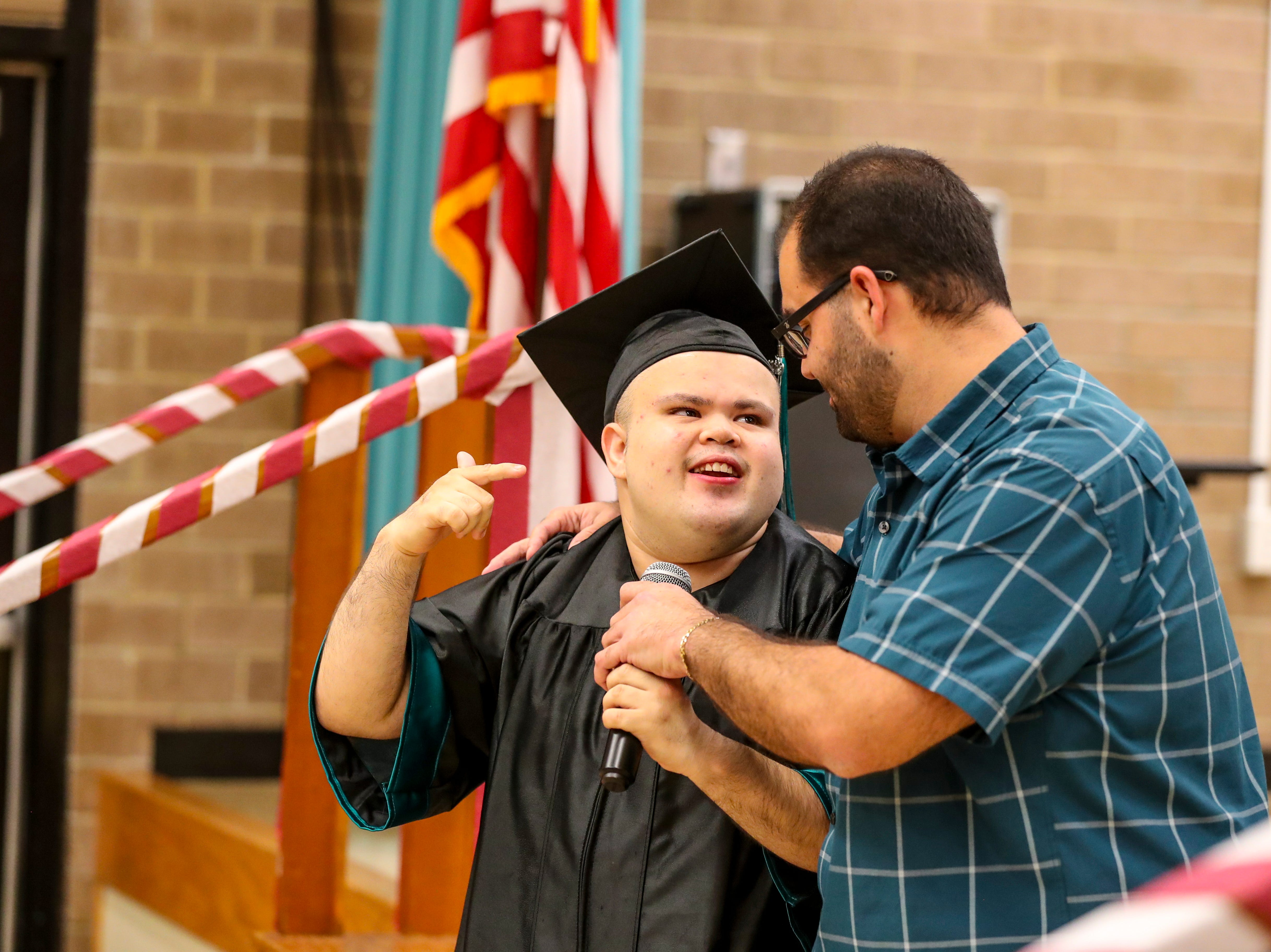Daviel Deras looks to Paraprofessional, Nick Brisebois, for help saying the Pledge of Allegiance to start the ceremony.  13 students at Buckingham Exceptional Student Center graduated during a ceremony in their honor. Family, friends, and staff were there to honor the graduates.
