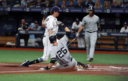 New York Yankees second baseman DJ LeMahieu (26) is safe at home plate as Tampa Bay Rays starting pitcher Tyler Glasnow (20) attempts to tag him out during the first inning at Tropicana Field.