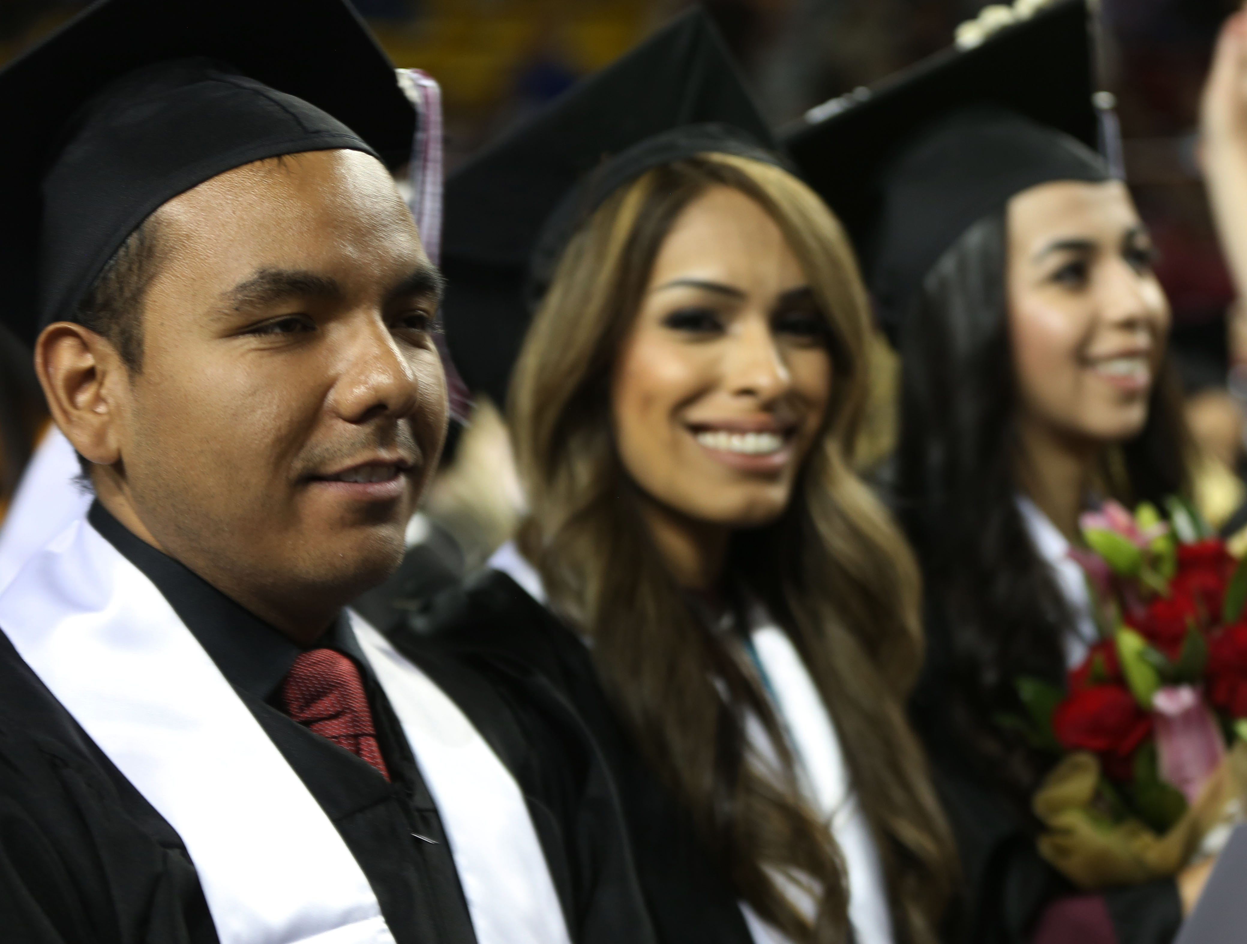 New Mexico State University graduates smile, after receiving their degrees during a graduation ceremony, Saturday May 11, 2019.