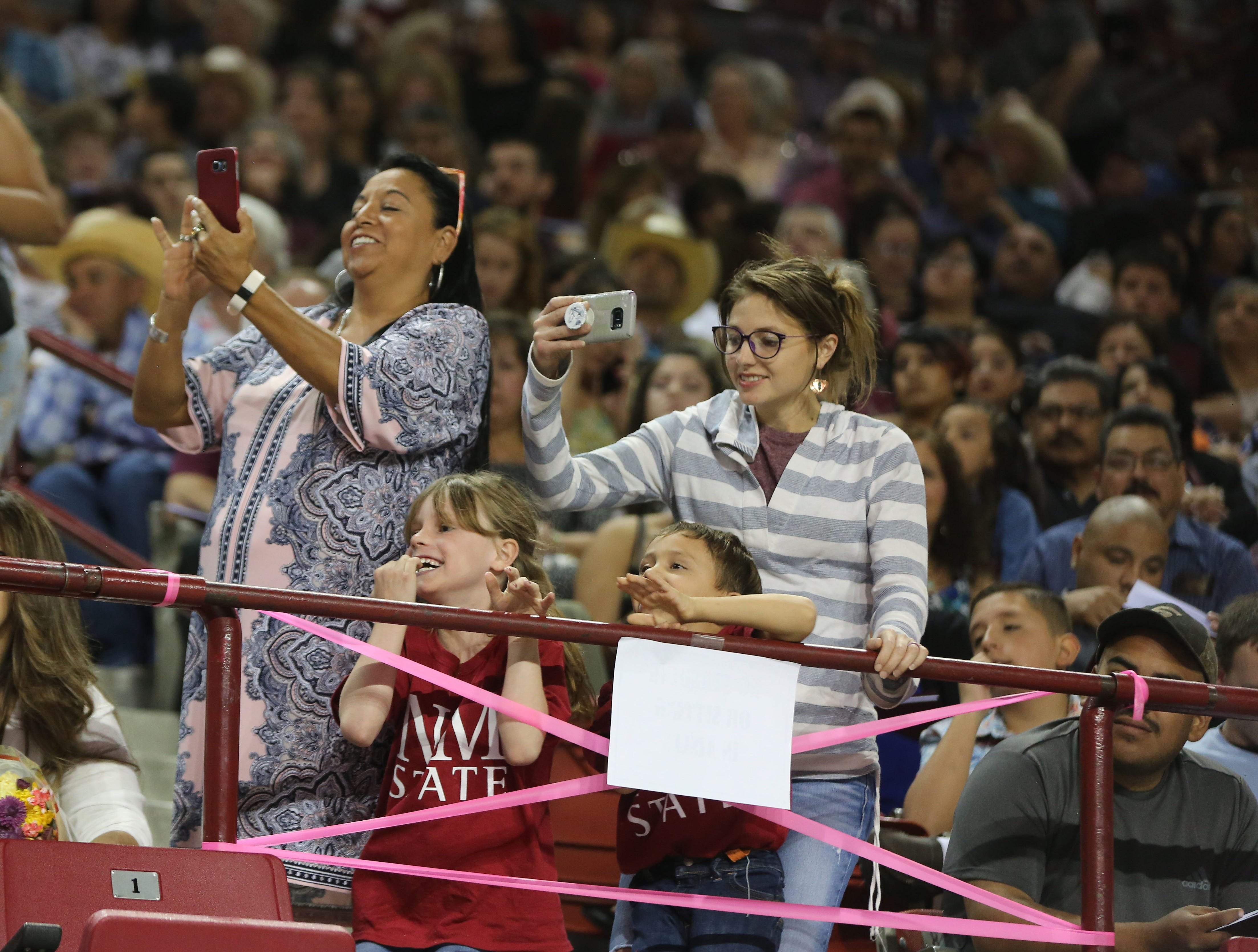 Family members of 2019 graduates cheer their loved ones on during the commencement ceremony, that was held at the Pan American building on the New Mexico State University campus.