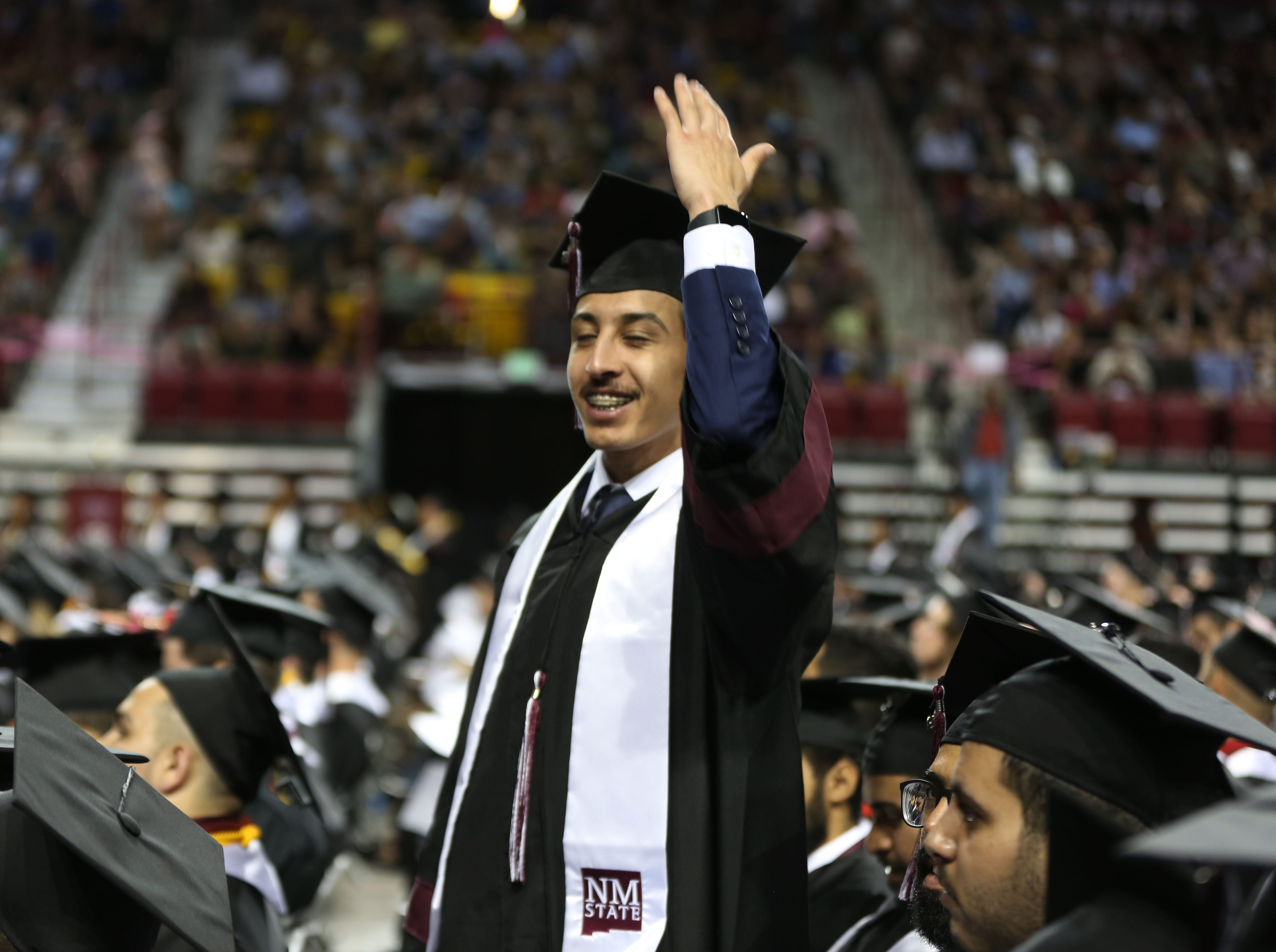 A New Mexico State University graduate, waves to the crowd after receiving his degree during the school's commencement ceremony, Saturday May 11, 2019.