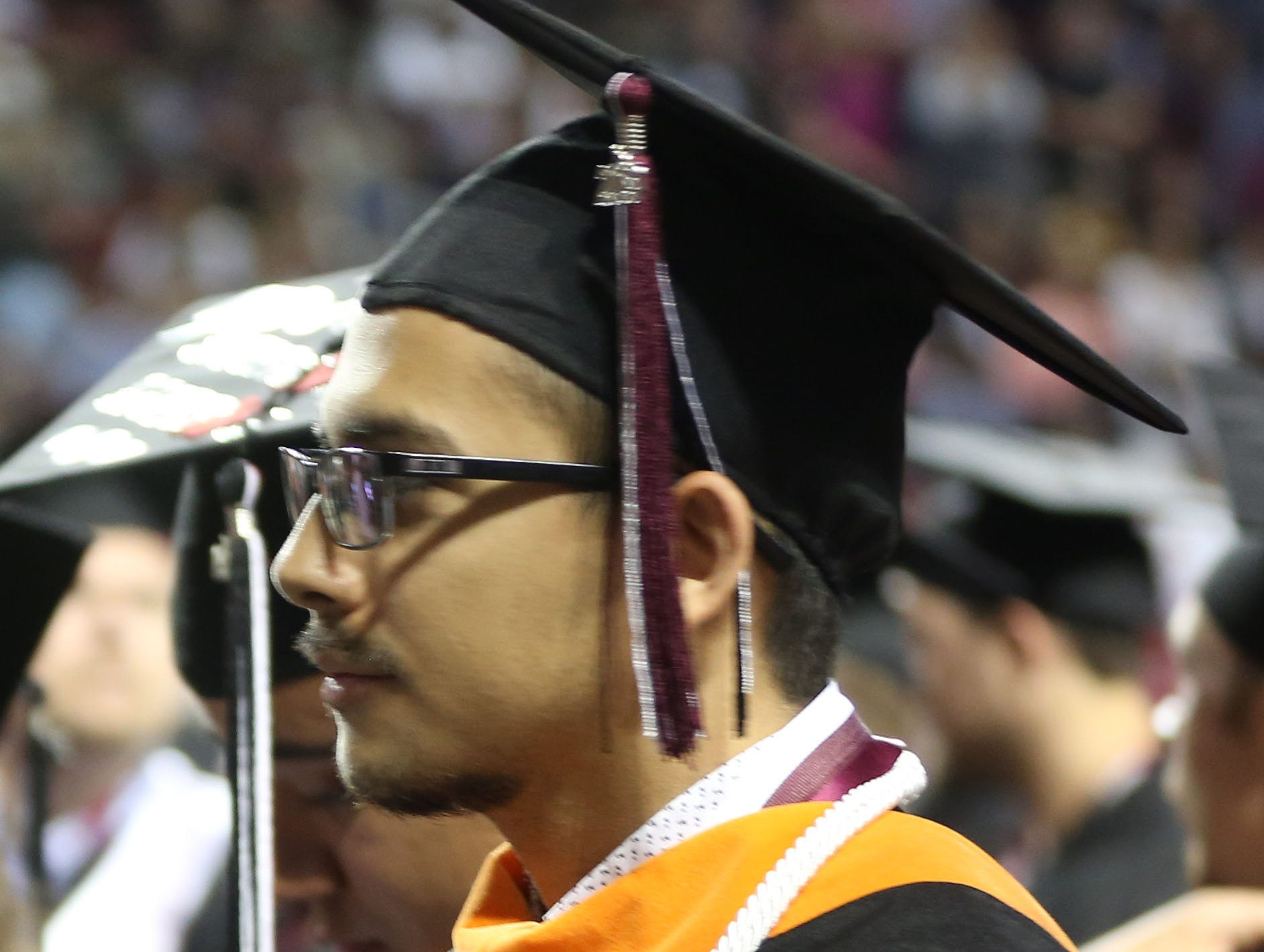 A New Mexico State University graduate, waits to exit the building after a morning commencement ceremony, Saturday May 11, 2019.
