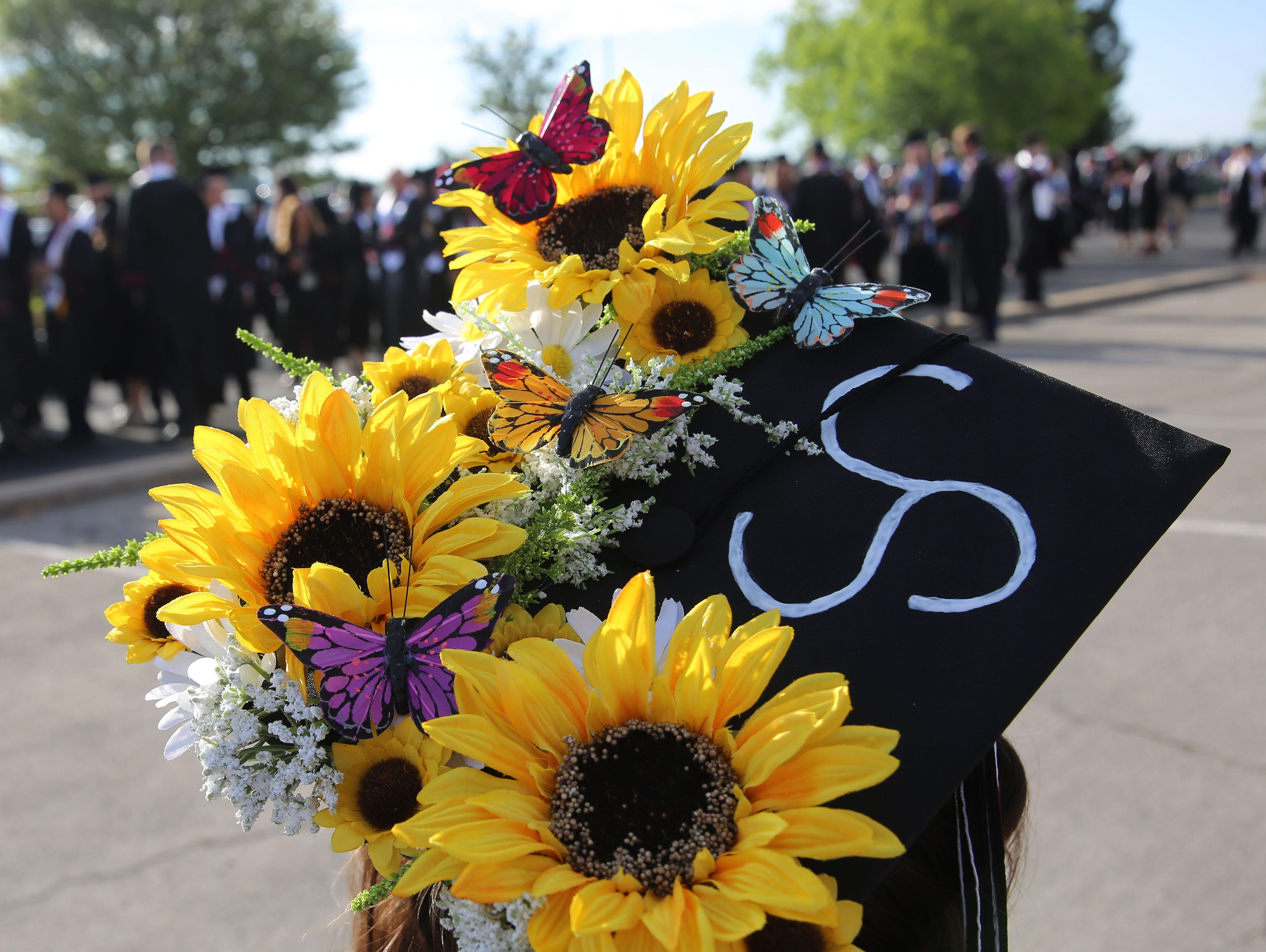 Jeanette Castanon majored in agricultural biology, after a recruiter at a college fair asked her if she'd heard about the degree program. She hadn't, but when she started taking classes, she fell in love with the field, she said. She hopes to work as an agricultural inspector. Her hat sports butterflies and sunflowers, because she took an entomology class, which she loved, and yellow is her favorite color.