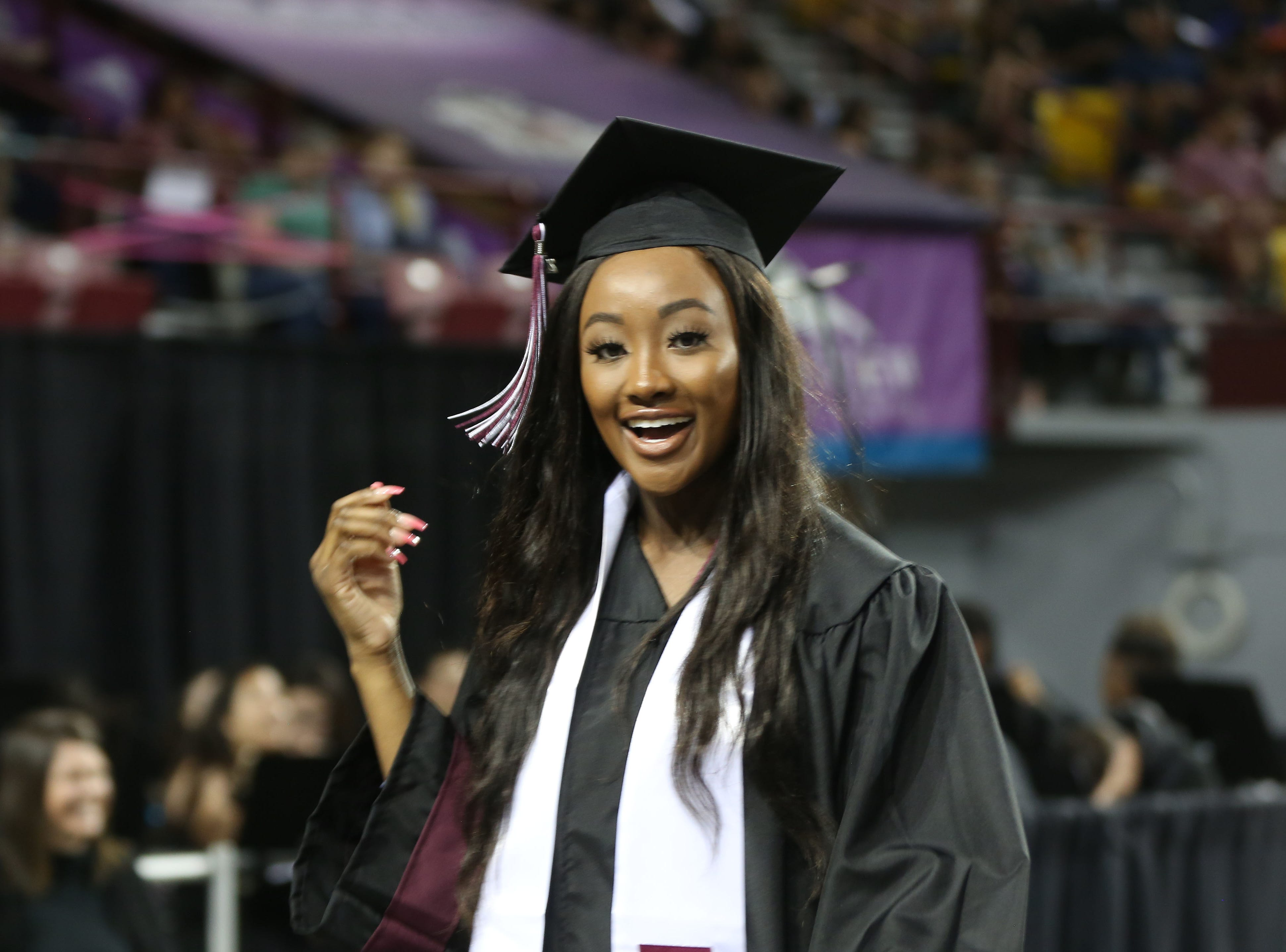 A New Mexico State University graduate smiles after receiving her degree at one of two commencement ceremonies hosted by the school, Saturday May 11, 2019.