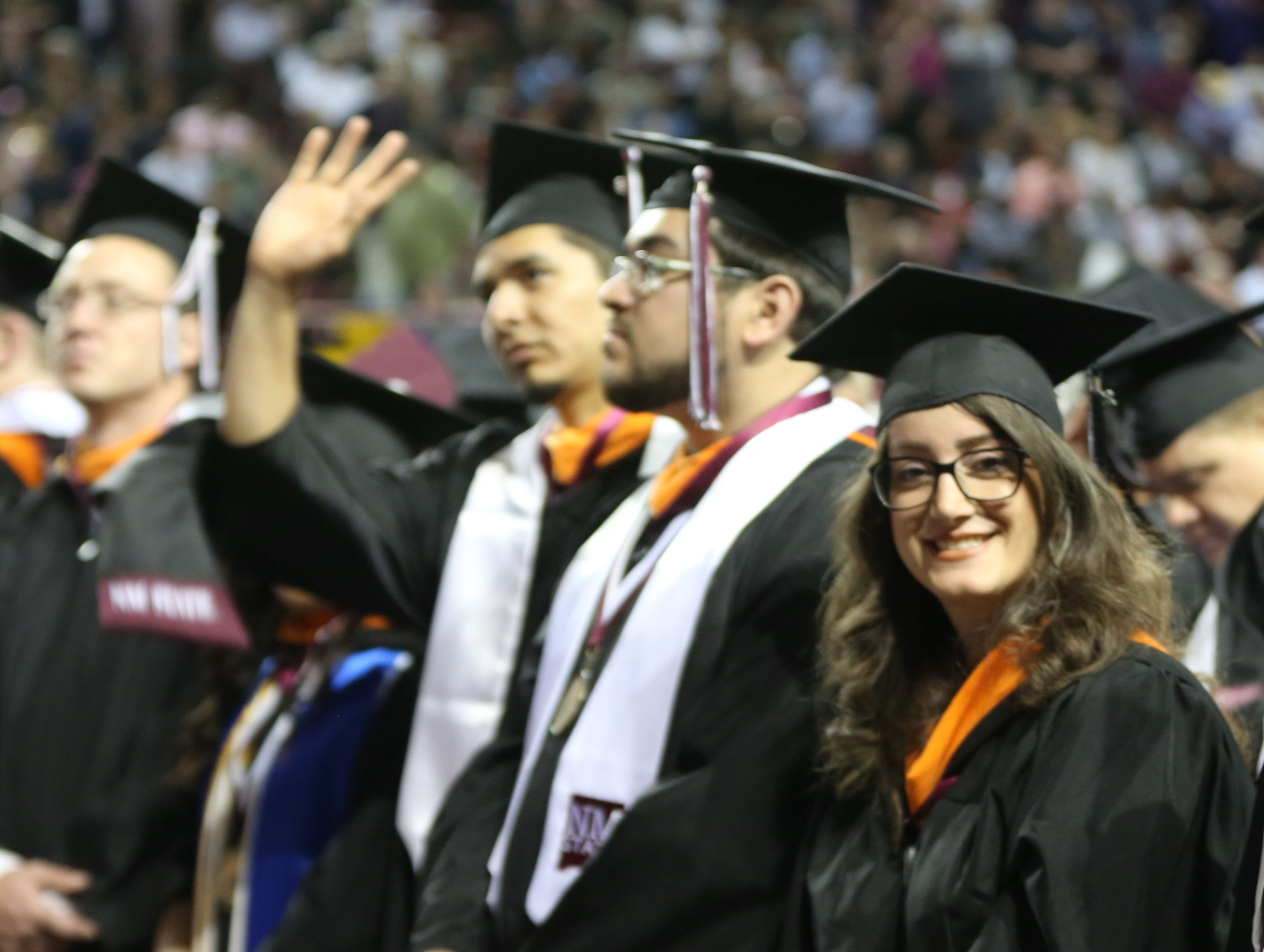 A student waives to friends and family, Saturday May 11, 2019, during New Mexico State Universities commencement ceremony.