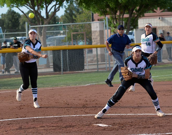 Oñate third baseman Madison Chavez (left) throws out the baserunner at first base as teammates Jaileen Mancha (center) and shortstop Samantha Barela look on.