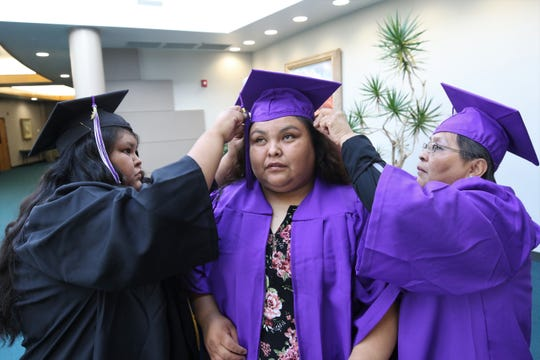 Lenorda Tacheenie, left, and Lenora Tacheenie, right, help Raylene Yazzie, center, with her cap in the Henderson Fine Arts Center before the San Juan College spring Commencement Ceremony on May 11. The sisters were graduating with their mother Lenora.