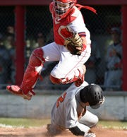 Mustang Nick Gattoni, bottom, scores a run by sliding under the tag of an airborne John Glenn catcher Josh Muse.