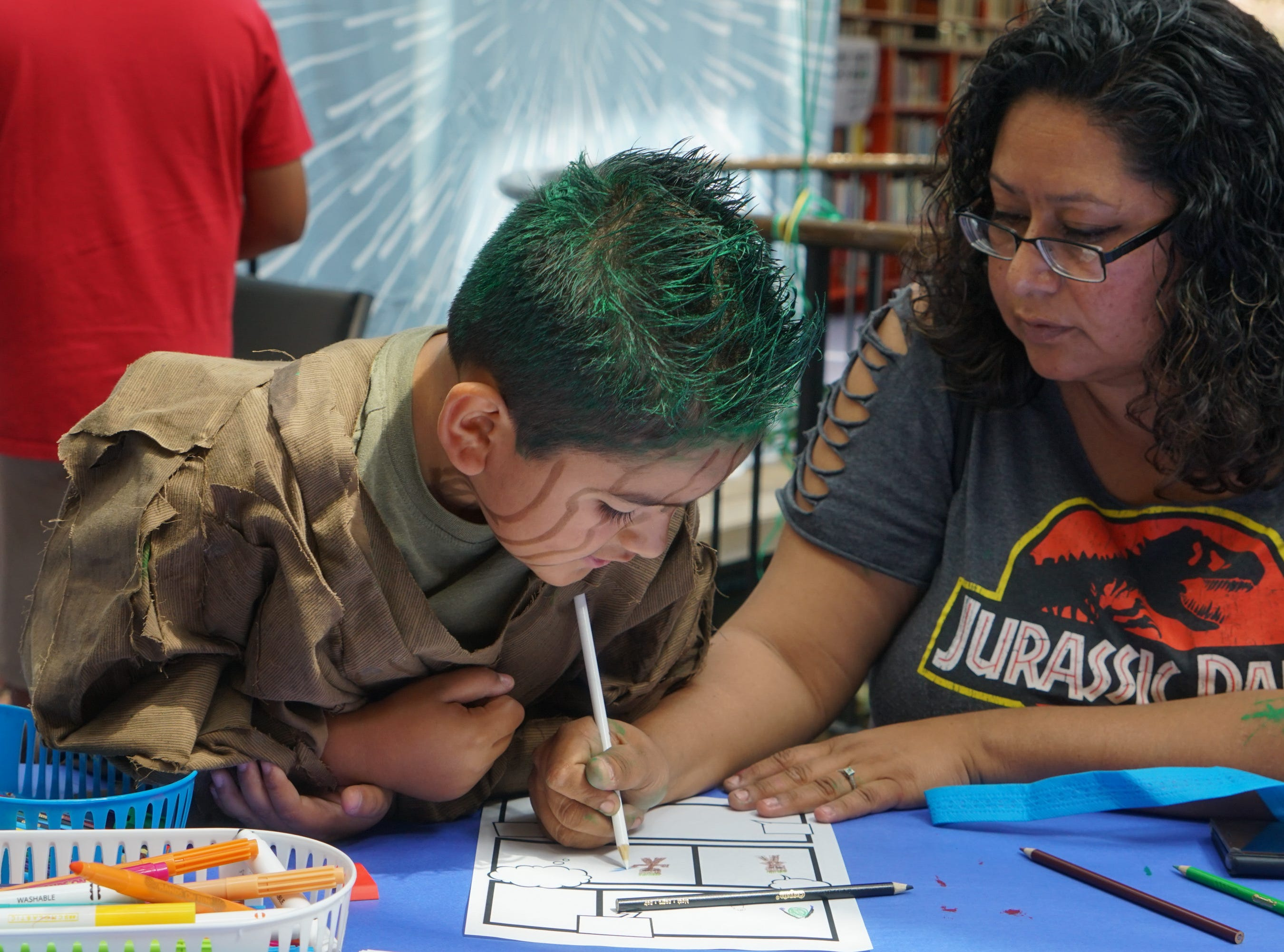 Adrian Rodriguez-Cesena draws with him mom, Elena Rodriguez, at the Palm Springs Public Library Comic Con, Palm Springs, Calif., May 11, 2019.