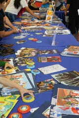 Attendees pick out items to add to swag bags at the Palm Springs Public Library Comic Con, Palm Springs, Calif., May 11, 2019.