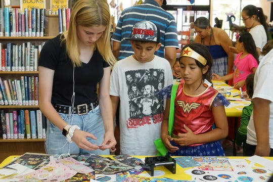Kids get guidance in pressing buttons at one of several activity tables at the Palm Springs Public Library Comic Con, Palm Springs, Calif., May 11, 2019.