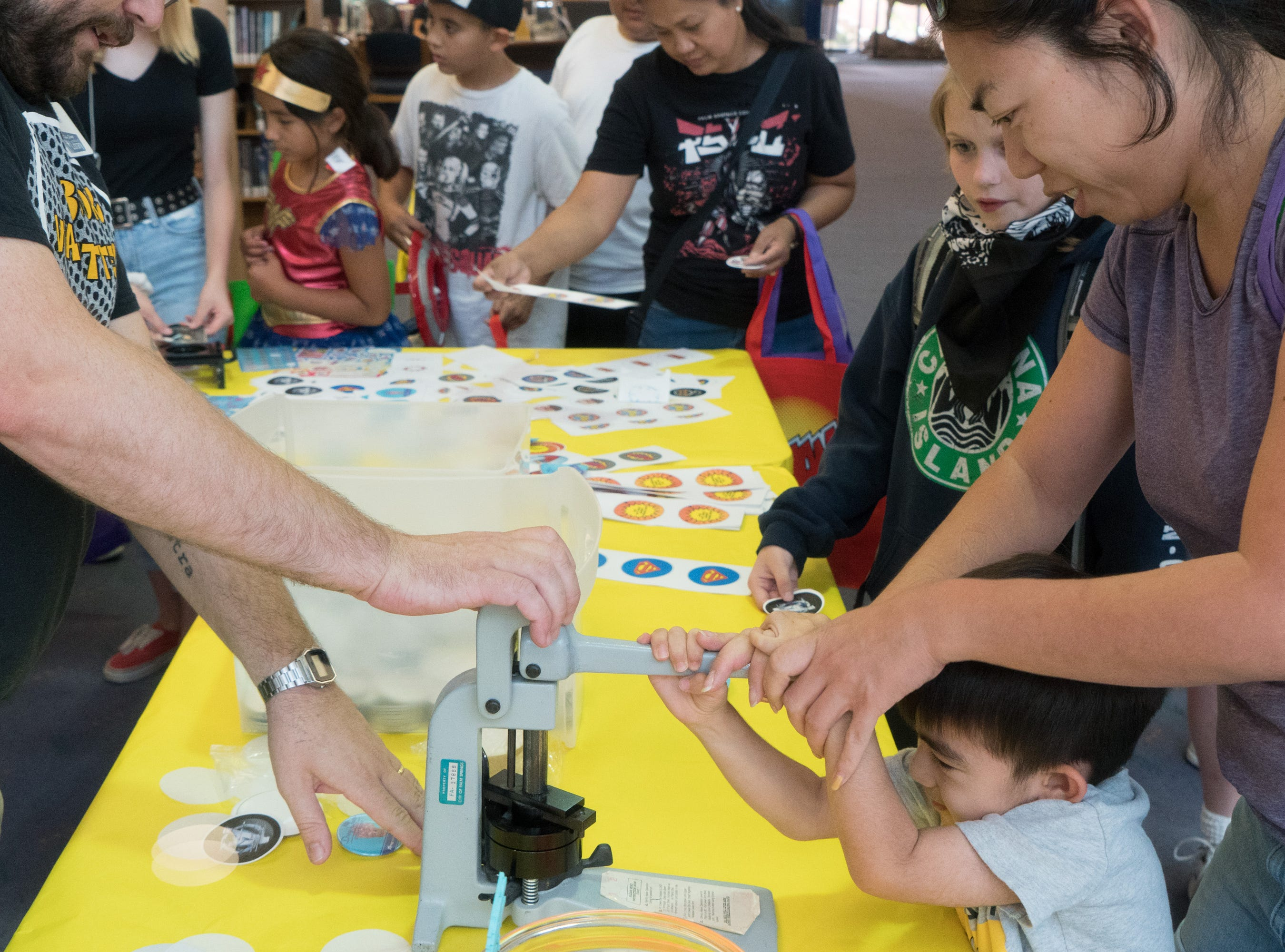 Kids press buttons at one of several activity tables at the Palm Springs Public Library Comic Con, Palm Springs, Calif., May 11, 2019.