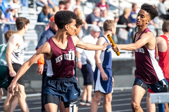 New Oxford's Tayshawn Golden hands off the baton to his brother Daywuan Golden in the boys' 3200m relay during the 2019 YAIAA Track and Field Championships at Dallastown High School Friday, May 10, 2019. New Oxford won the event in 8:18.55.