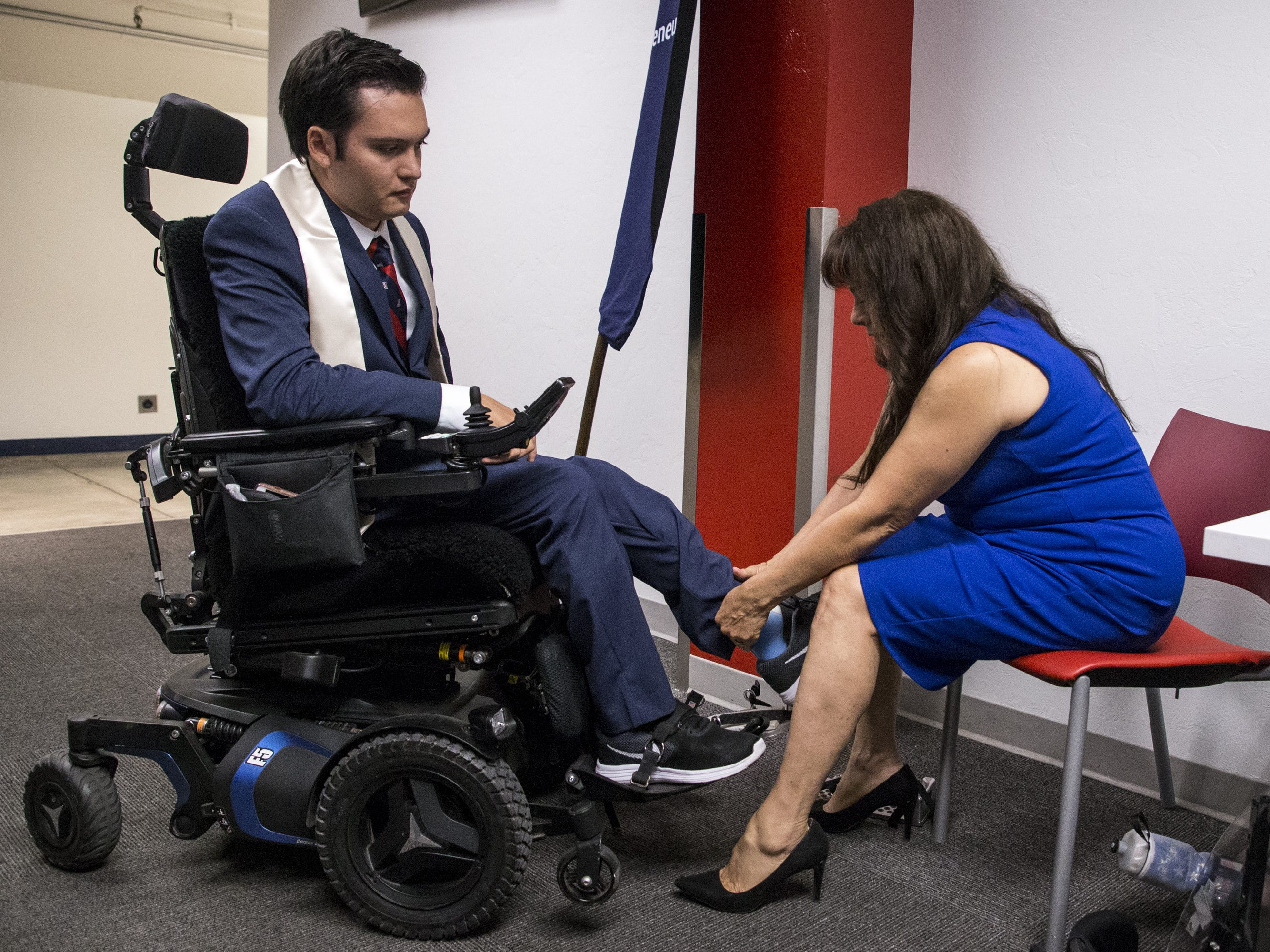 Hermelinda Bristol helps her son, Jeffrey, 24, stand up as he is recognized during University of Arizona's Eller College of Management convocation on Saturday, May 11, 2019, at McKale Memorial Center in Tucson, Ariz. Bristol, who was diagnosed with cavernous angioma as a child, has begun to learn how to walk with the help of an exoskeleton created as part of an engineering school design program.