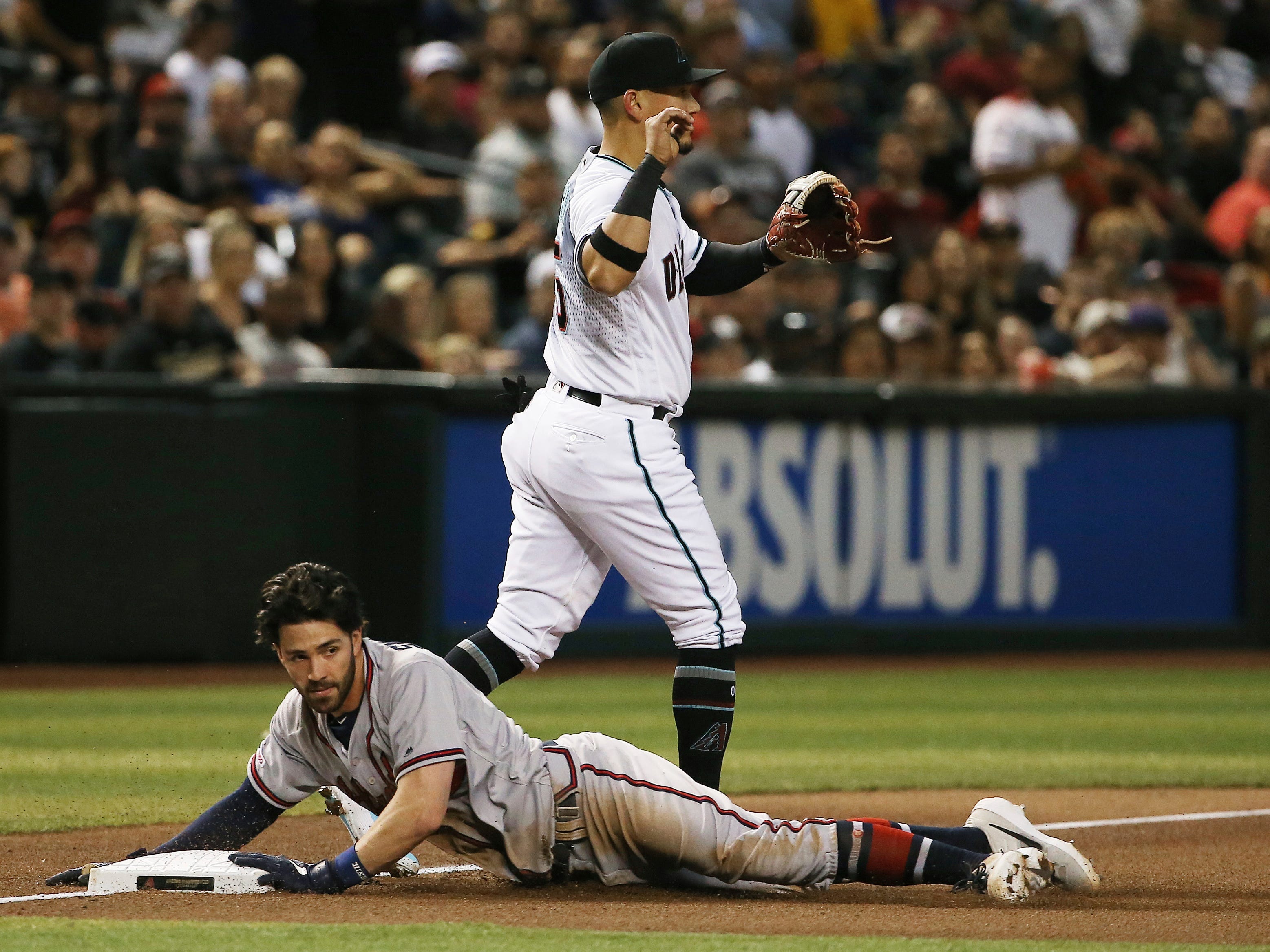 Atlanta Braves' Dansby Swanson, left, slides safely into third base with a triple as Arizona Diamondbacks third baseman Ildemaro Vargas, back, waits for a late throw during the fourth inning of a baseball game Friday, May 10, 2019, in Phoenix. (AP Photo/Ross D. Franklin)