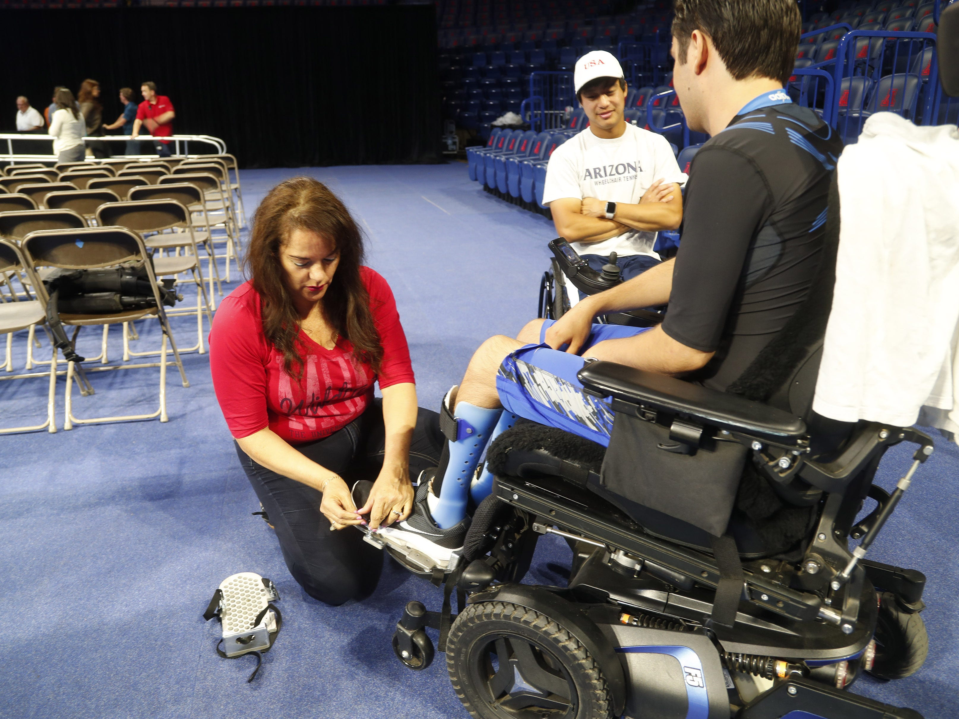 University of Arizona graduate Jeffrey Bristol has supports placed on his feet by his mom, Hermelinda, at McKale Center in Tucson, Ariz. on May 8, 2019. He has cerebral palsy and is a lifelong wheelchair user but has learned to walk with the help from engineering students who helped construct an exoskeleton.