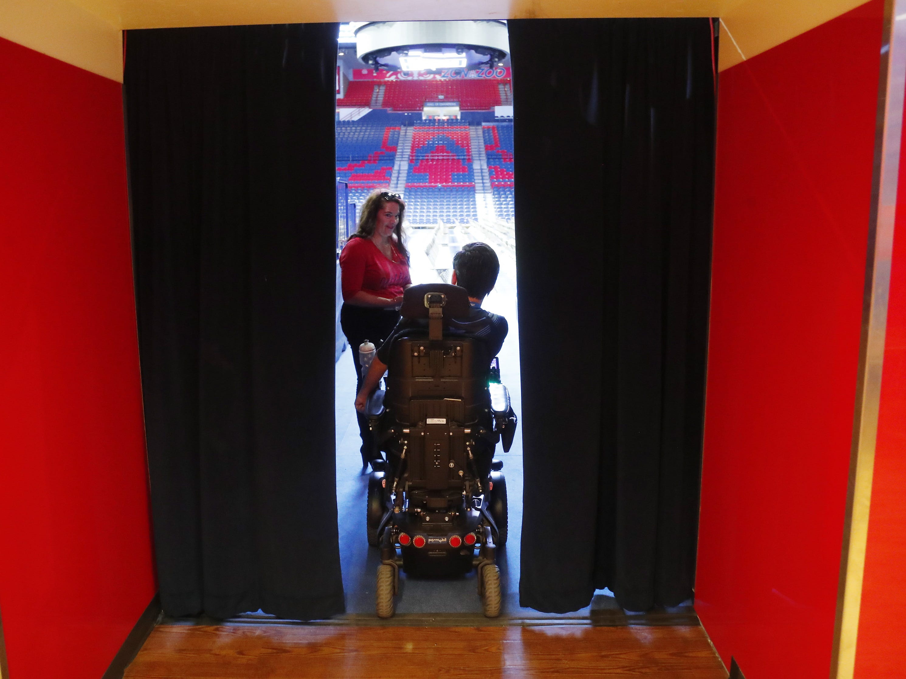 University of Arizona graduate Jeffrey Bristol waits in a breezeway with his mom, Hermelinda, at McKale Center in Tucson, Ariz. on May 8, 2019. He has cerebral palsy and is a lifelong wheelchair user but has learned to walk with the help from engineering students who helped construct an exoskeleton. He plans to walk for graduation.