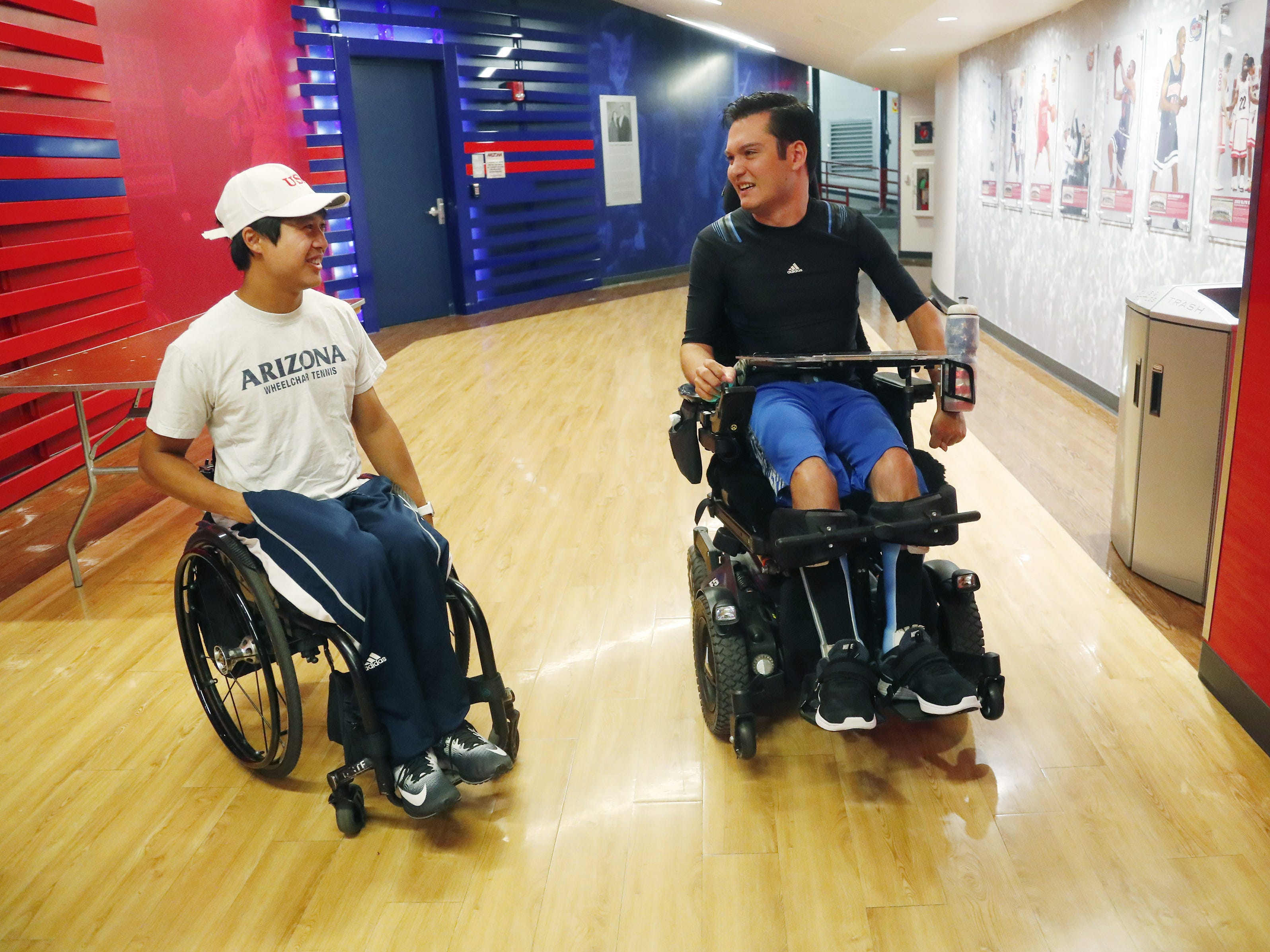 University of Arizona graduate Jeffrey Bristol (right) talks with Jason Keatseansilp at McKale Center in Tucson, Ariz. on May 8, 2019. Bristol has cerebral palsy and is a lifelong wheelchair user but has learned to walk with the help from a team of engineering students, including Keatseansilp, who helped construct an exoskeleton. Bristol plans on walking for graduation.