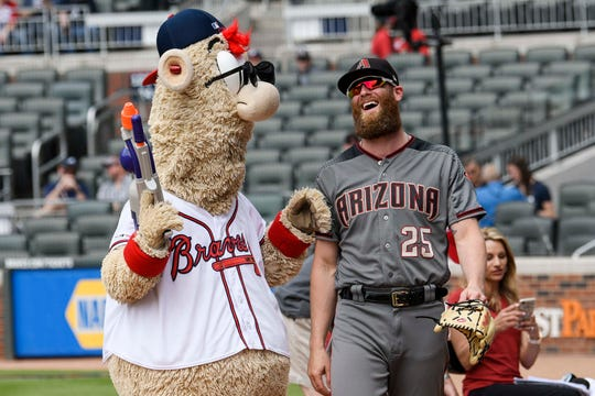 Braves mascot Blooper and Archie Bradley interact on the field prior to a game in Atlanta last month.