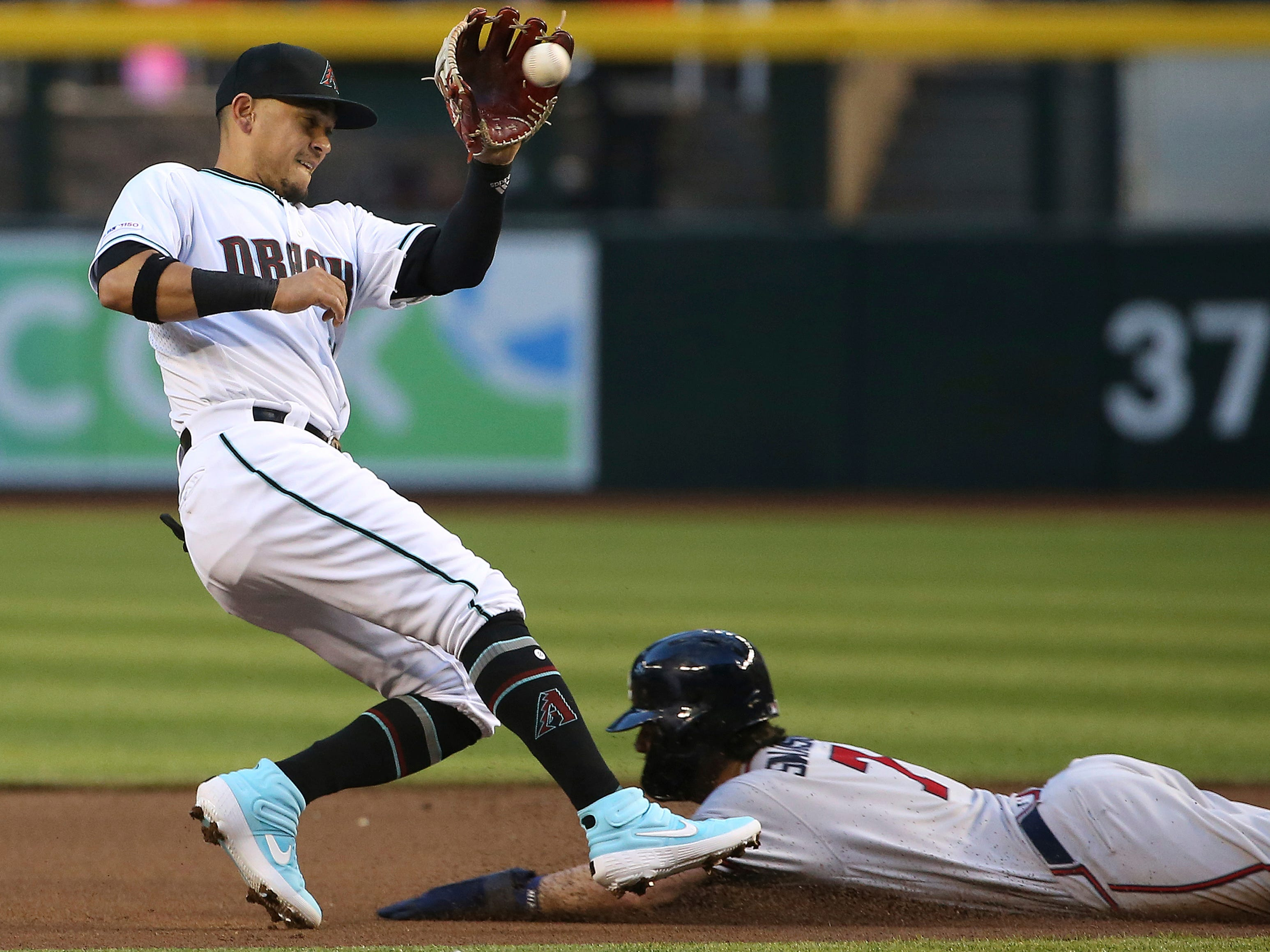 Arizona Diamondbacks third baseman Ildemaro Vargas, left, makes a catch on the ball before tagging out Atlanta Braves shortstop Dansby Swanson (7) as Swanson tried to steal second base during the first inning of a baseball game Friday, May 10, 2019, in Phoenix. (AP Photo/Ross D. Franklin)