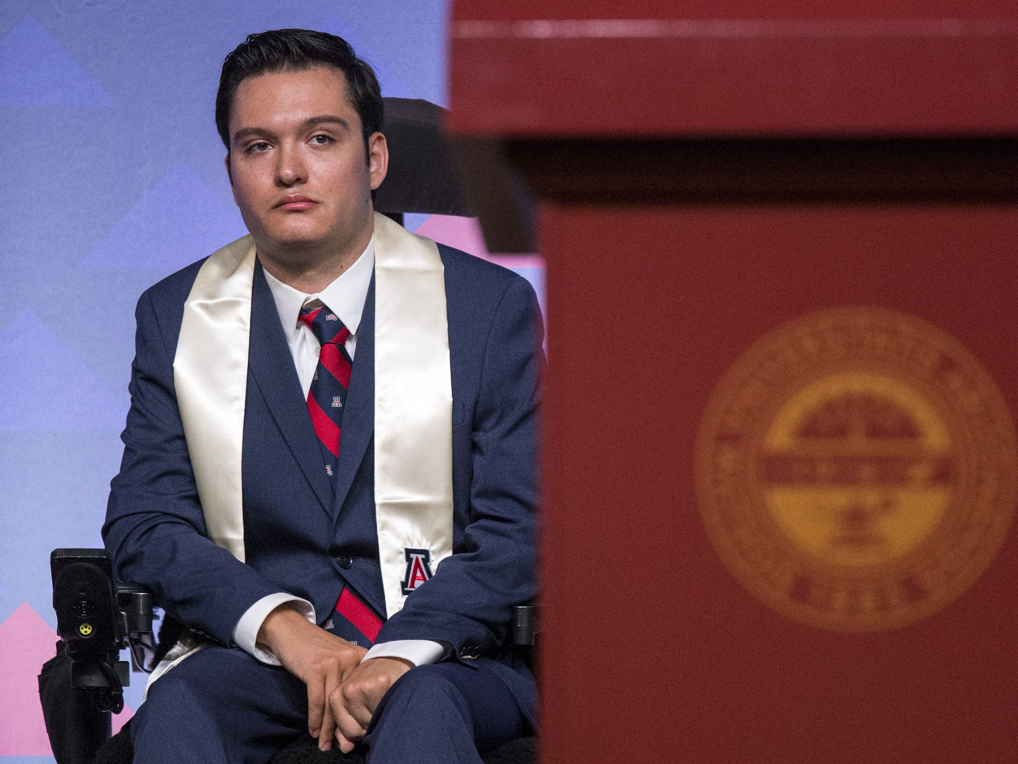 Jeffrey Bristol, 24, listens during University of Arizona's Eller College of Management convocation on Saturday, May 11, 2019, at McKale Memorial Center in Tucson, Ariz. Bristol, who was diagnosed with cavernous angioma as a child, has begun to learn how to walk with the help of an exoskeleton created as part of an engineering school design program.