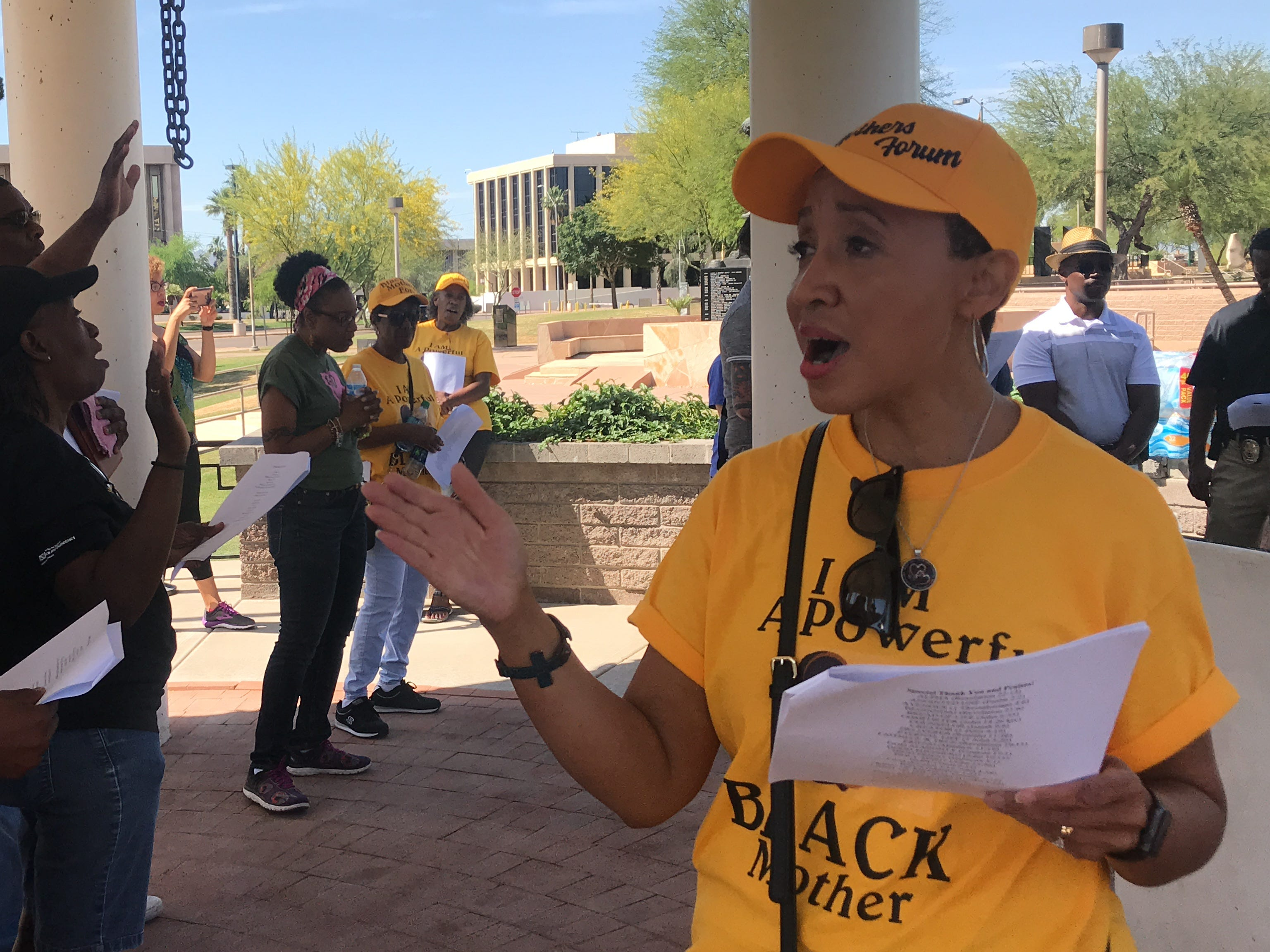 Janelle Wood (right), founder of Black Mothers Forum, leads a group of people in song at Wesley Bolin Memorial Plaza in Phoenix on May 11, 2019.