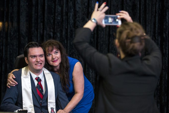 Adrienne Barela takes a photo of Jeffrey Bristol, 24, and his mother, Hermelinda, before University of Arizona's Eller College of Management convocation on Saturday, May 11, 2019, at McKale Memorial Center in Tucson, Ariz. Bristol, who was diagnosed with cavernous angioma as a child, has begun to learn how to walk with the help of an exoskeleton created as part of an engineering school design program.