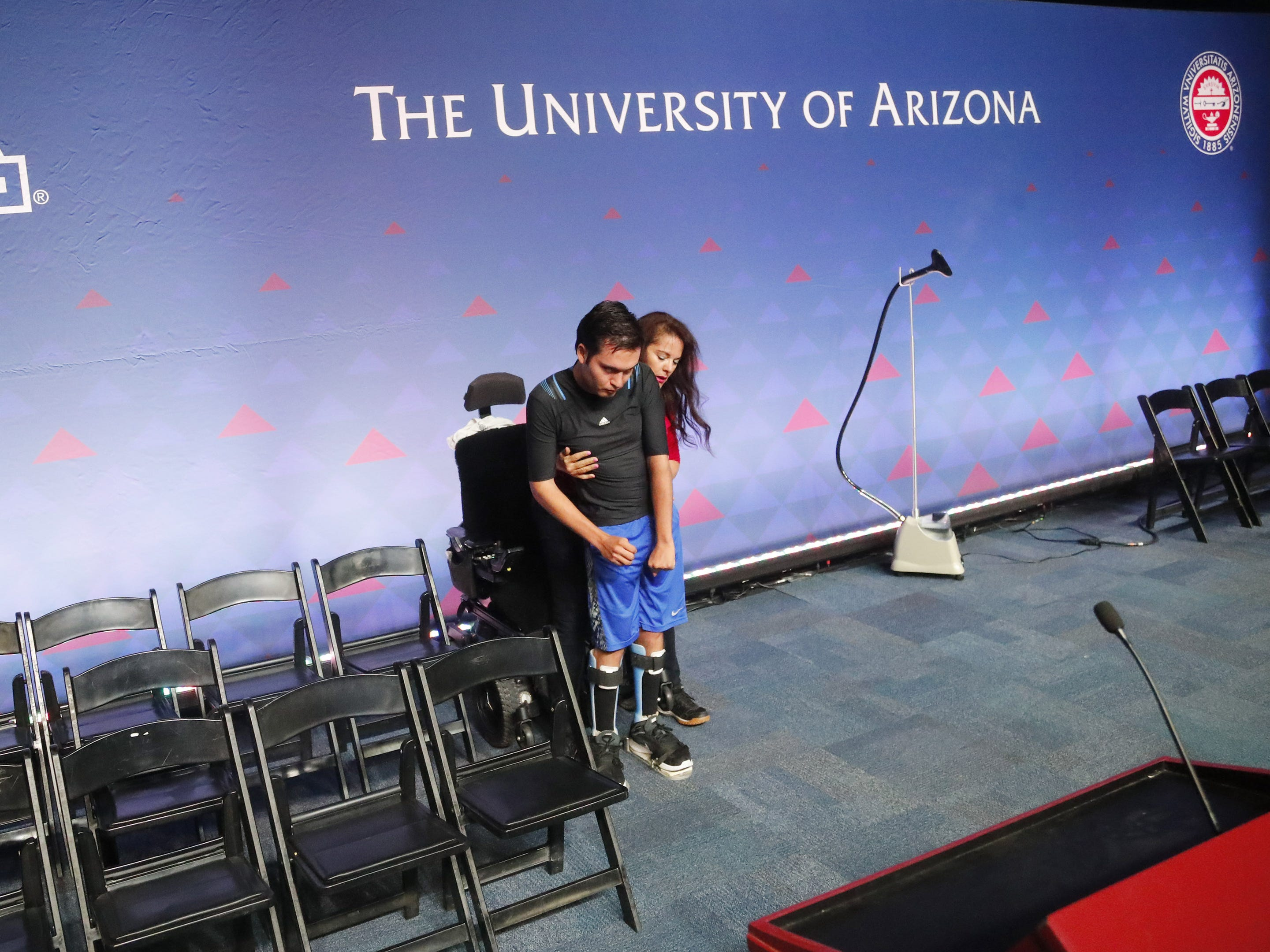 University of Arizona graduate Jeffrey Bristol practices walking on stage with his mom, Hermelinda, at McKale Center in Tucson, Ariz. on May 8, 2019. He has cerebral palsy and is a lifelong wheelchair user but has learned to walk with the help from engineering students who helped construct an exoskeleton. He plans on walking for graduation.