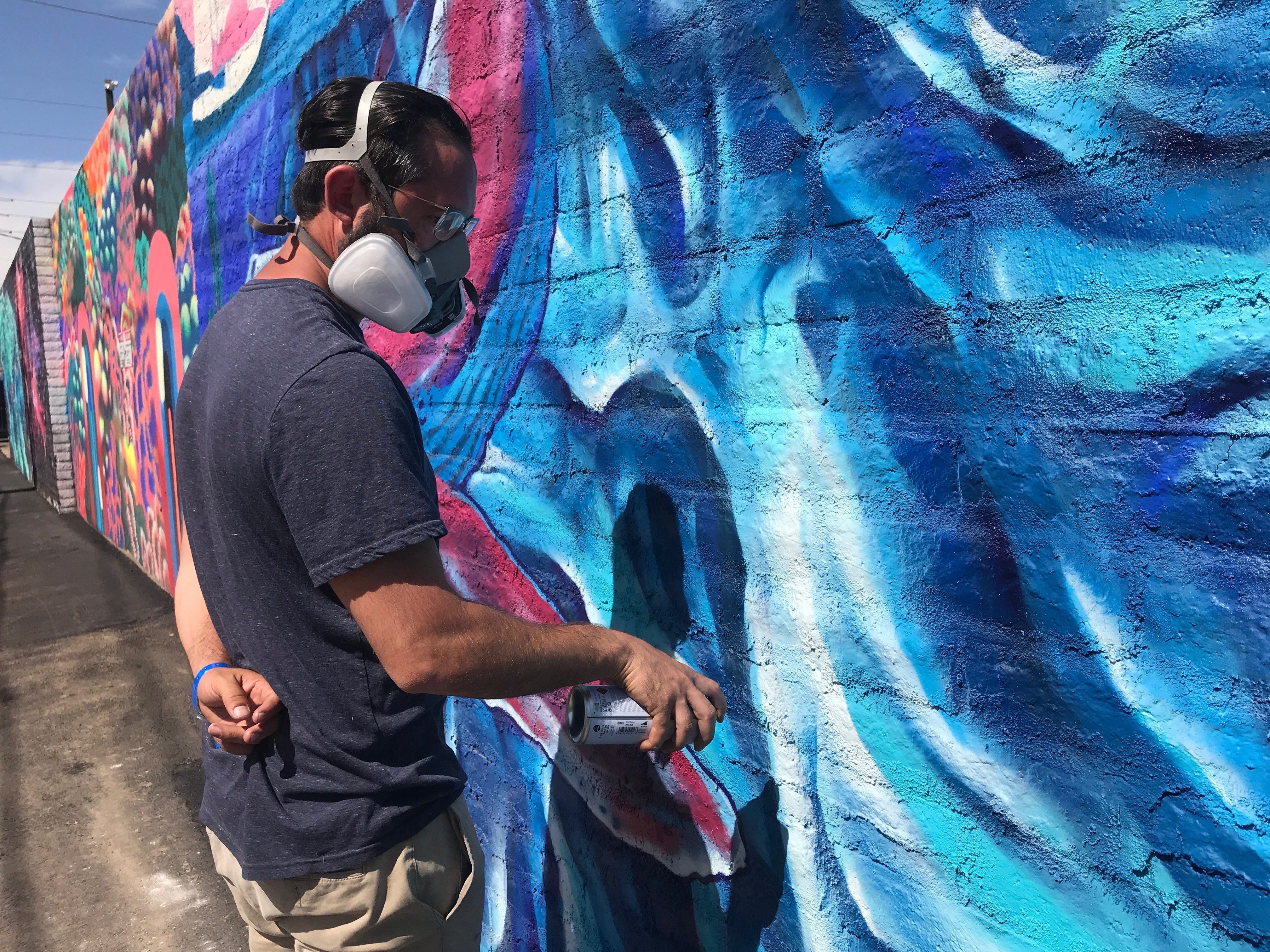 Isaac Caruso paints his section of the mural behind The Churchill near First and McKinley streets on Saturday, May 11, 2019.
