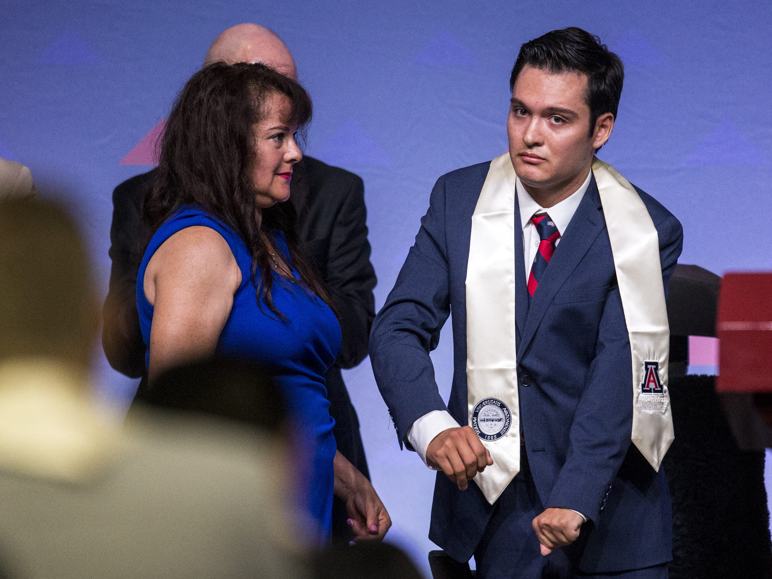 Hermelinda Bristol watches as her son, Jeffrey, 24, is recognized during University of Arizona's Eller College of Management convocation on Saturday, May 11, 2019, at McKale Memorial Center in Tucson, Ariz. Bristol, who was diagnosed with cavernous angioma as a child, has begun to learn how to walk with the help of an exoskeleton created as part of an engineering school design program.