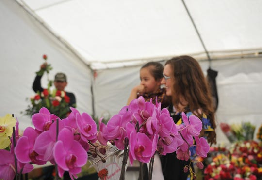 Laura Carrillo holds her niece while helping to sell Mother's Day flowers.