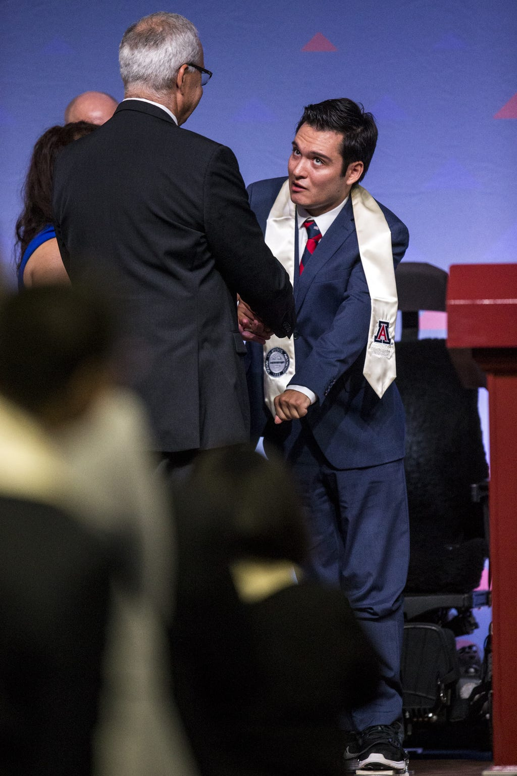 Jeffrey Bristol, 24, shakes hands with University of Arizona's Eller College of Management Dean Paulo Goes during convocation on Saturday, May 11, 2019, at McKale Memorial Center in Tucson, Ariz. Bristol, who was diagnosed with cavernous angioma as a child, has begun to learn how to walk with the help of an exoskeleton created as part of an engineering school design program.