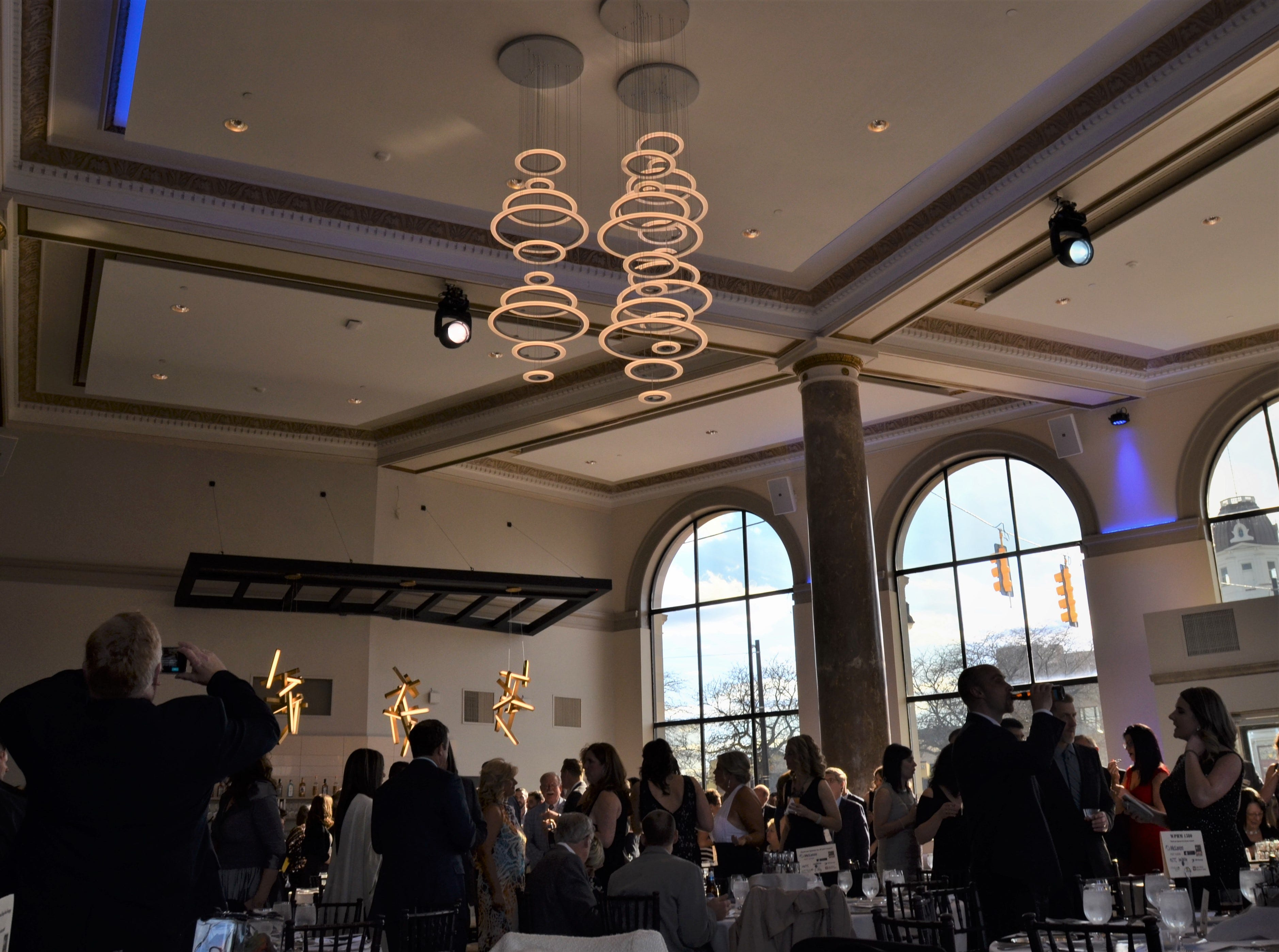 A man takes a photo of the debuting ballroom in the CityFlats Hotel on Friday, May 10, 2019. The venue features hanging light fixtures and colored lighting that can be changed for events.