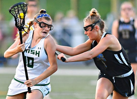 York Catholic's Sydney Mentzer, left, controls the ball while Kennard-Dale's Megan Halczuk defends during girls' lacrosse championship action at Eastern York Senior High School in Wrightsville, Friday, May 10, 2019. Kennard-Dale would win the title game 11-10. Dawn J. Sagert photo