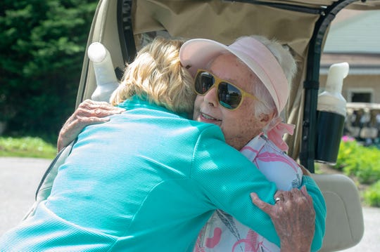 Janet Pope gets a birthday hug from a member of the Out Door Country Club's 18-hole group on her 90th birthday Saturday, May 11, 2019.