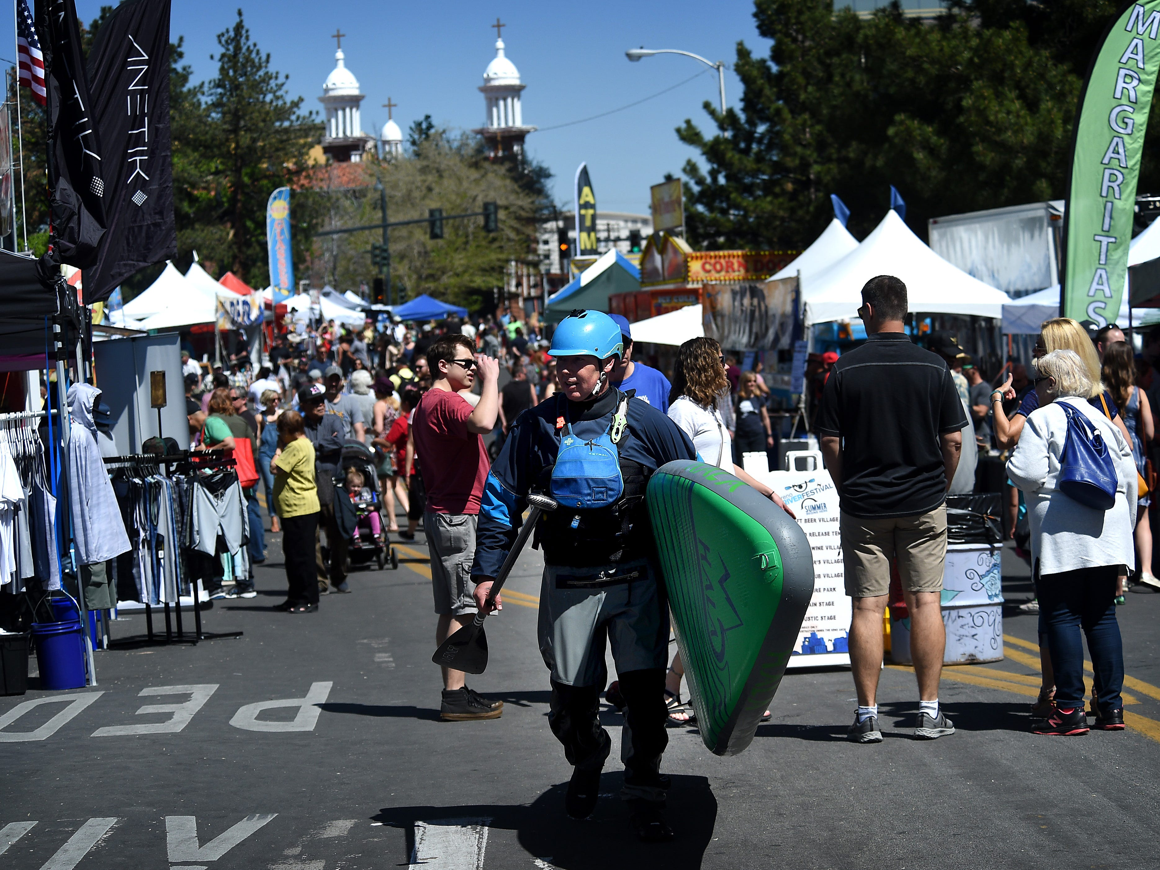 A stand up paddle boarder walks down Arlington Ave. during the Reno River Festival on the Truckee River in Wingfield Park on May 11, 2019.