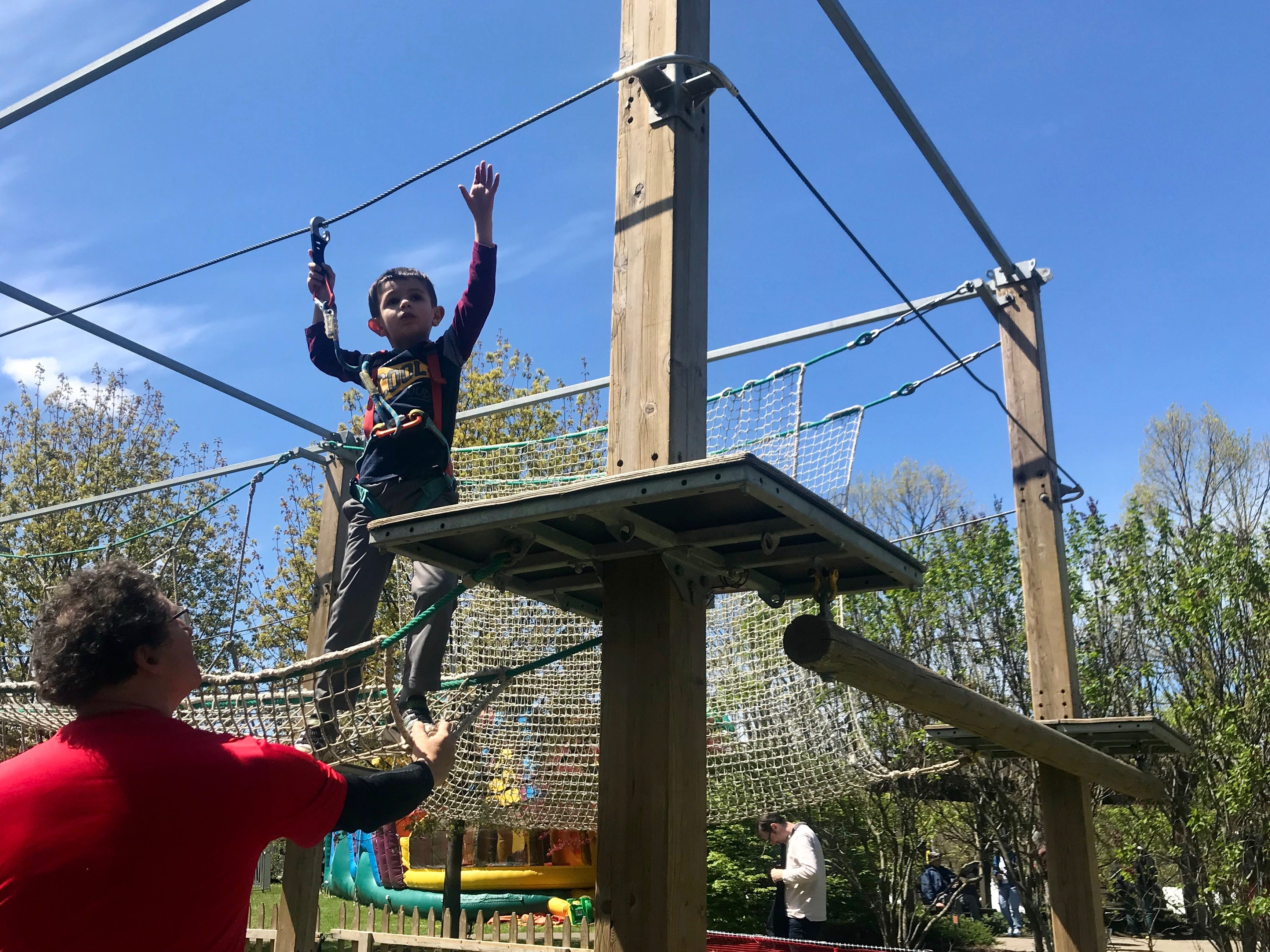 Antonio Marzovilla, 5, of Webster, climbs a ropes course at the Rochester Lilac Festival on Saturday.