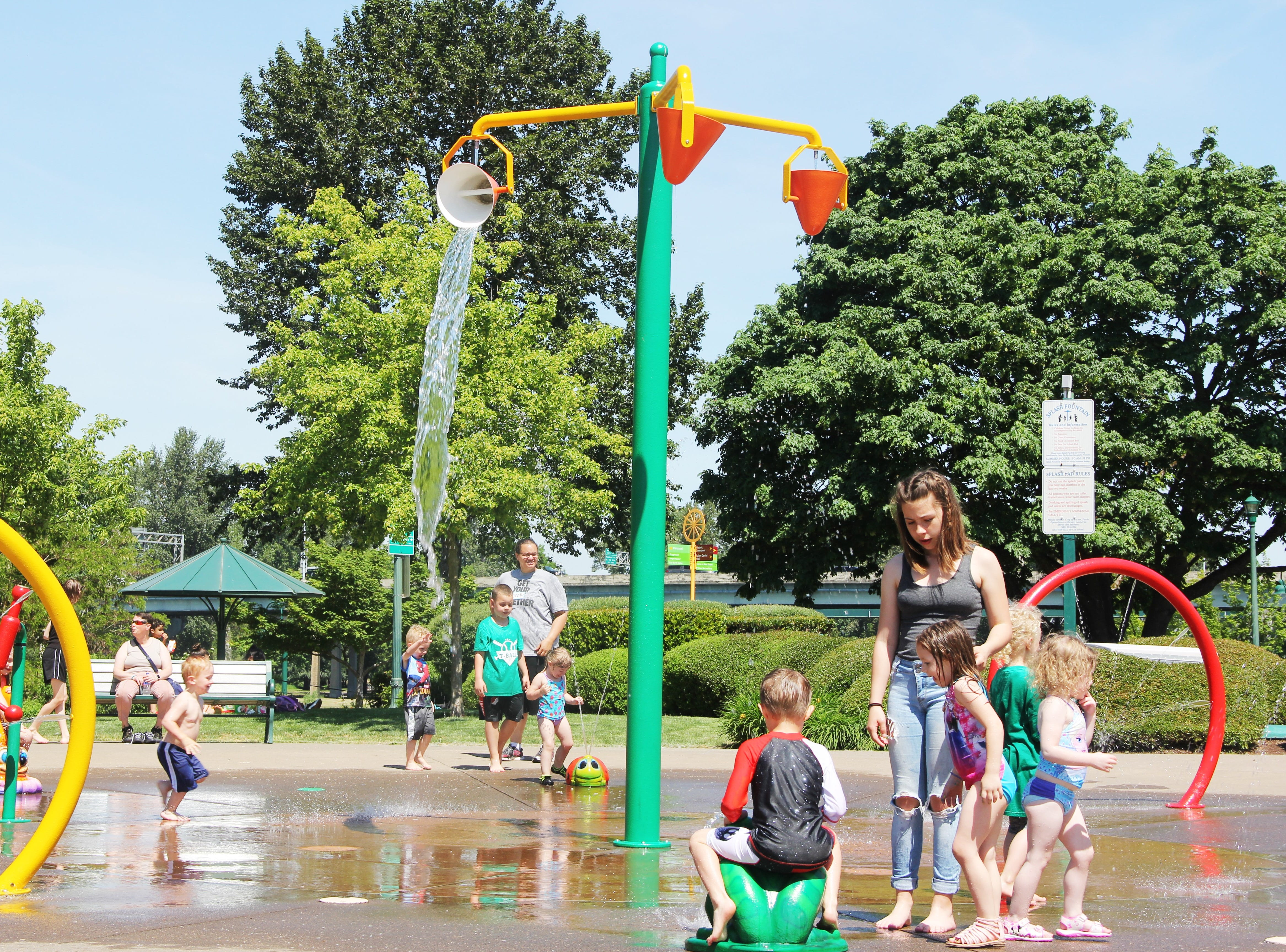 Kids and parents cool off at the Riverfront Park splash fountain in Salem on May 11, 2019. Two splash fountain locations, Riverfront Park and River Road Park, opened for the first time this season Saturday.