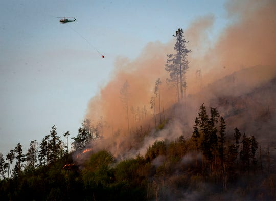 A helicopter heads back to a water source to get more water to dump on a wildfire near the Dorena Grange near Cottage Grove, Ore., May 10, 2019.