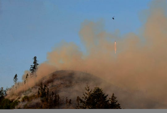 A helicopter drops water on a wildfire near the Dorena Grange near Cottage Grove, Ore.,  May 10, 2019.