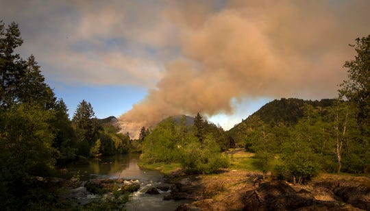 A wildfire burns on a hillside near the Row River near Cottage Grove, Ore., Friday, May 10, 2019.