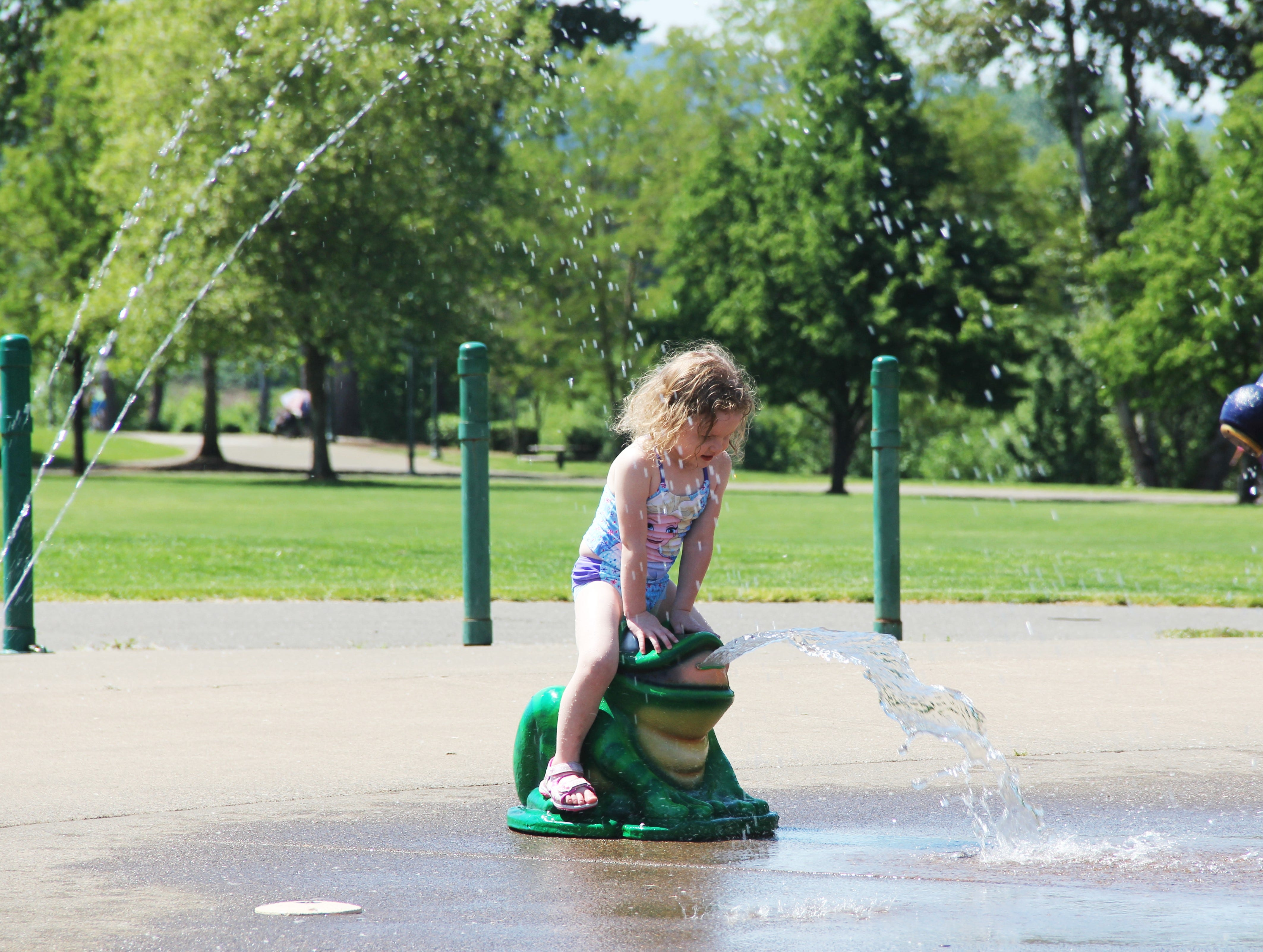 Scarlett Gauzner, 3, of Salem, sits on a frog at the Riverfront Park splash fountain in Salem on May 11, 2019.
