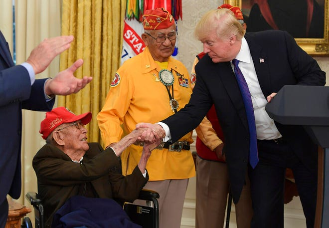 In this Monday, Nov. 27, 2017, file photo, President Donald Trump meets with Navajo Code Talkers, Fleming Begaye Sr., seated and Thomas Begay, center, in the Oval Office of the White House in Washington. World War II-era Navajo Code Talker Fleming Begaye, Sr., passed away on Friday, May 10, 2019, at the age of 97, in Chinle, Ariz.